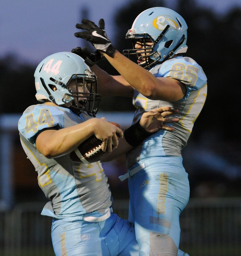 Maine West's Jake Bellizzi (left) celebrates a touchdown with teammate Costa Paschos against Elk Grove earlier this season. The Warriors host Benet in a Class 7A first round playoff game Friday night in Des Plaines.