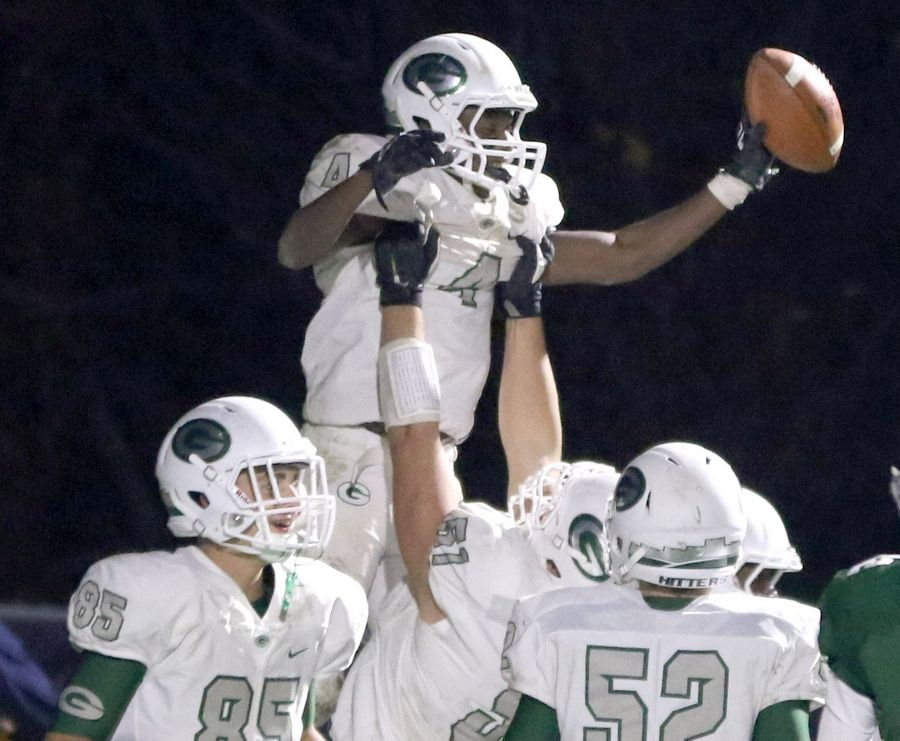 Glenbard West's Tyquan Cox gets a lift after scoring a touchdown during first round playoff football action at Bartlett Friday night.