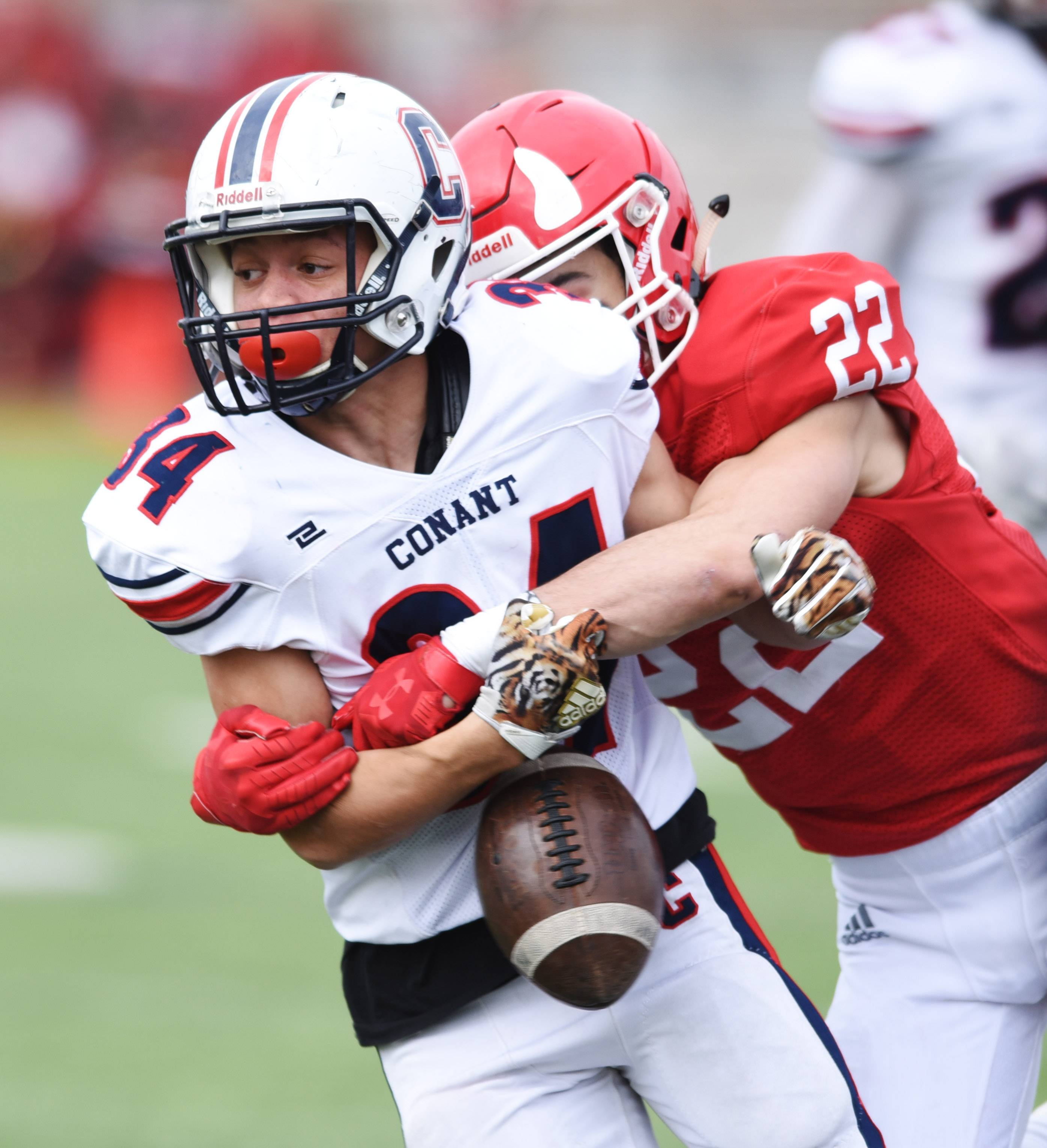 The ball pops loose from the grasp of Conant's Bradley Spates as he is tackled by Hinsdale Central's Jack McCarty, but the fumble goes out of bounds and the Cougars retain possession during Saturday's Class 8A playoff game in Hinsdale.
