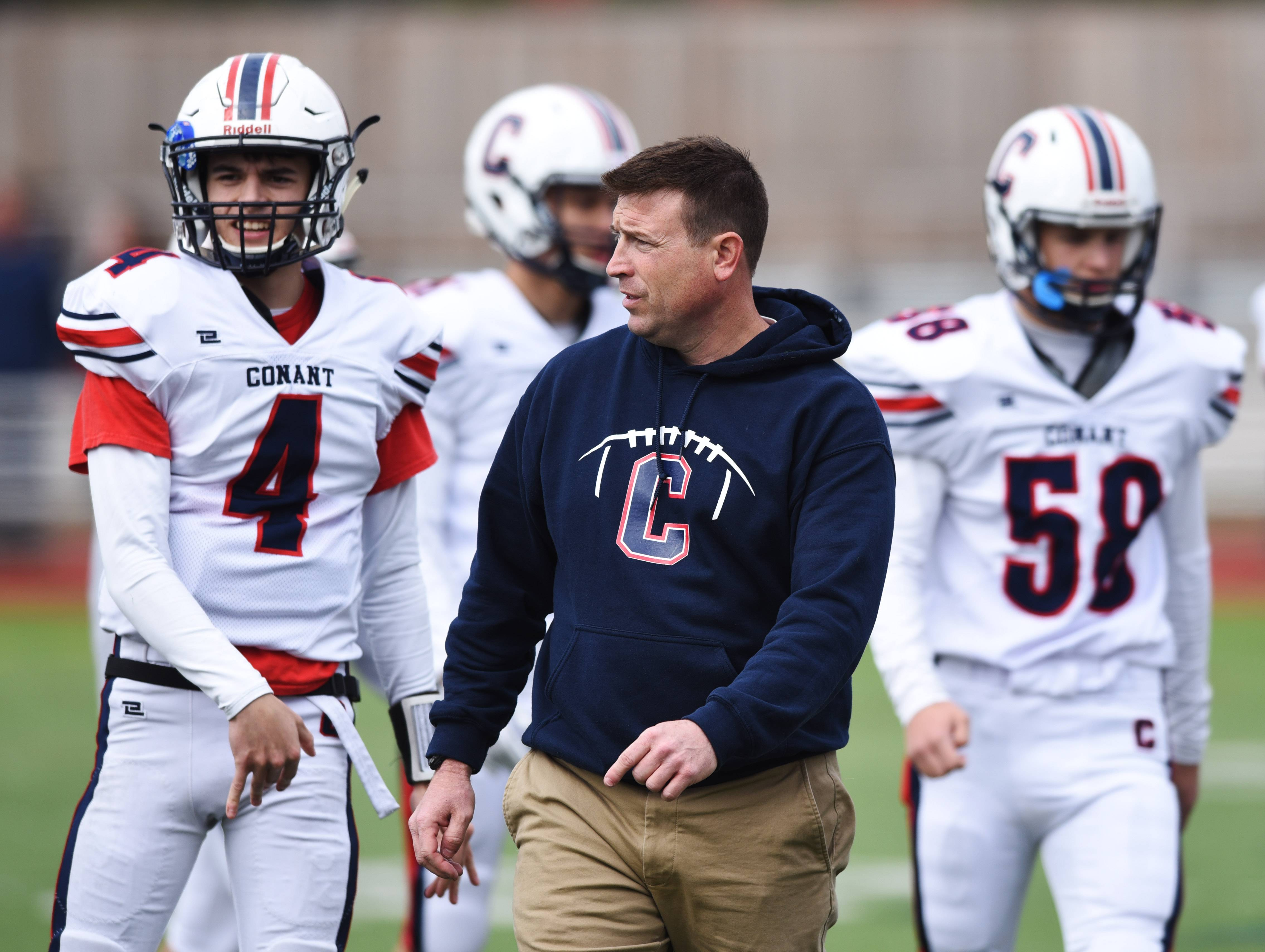 Conant head coach Bryan Stortz talks to his team, including quarterback Kevin Polaski, left, during a timeout in Saturday's Class 8A playoff game against Hinsdale Central.