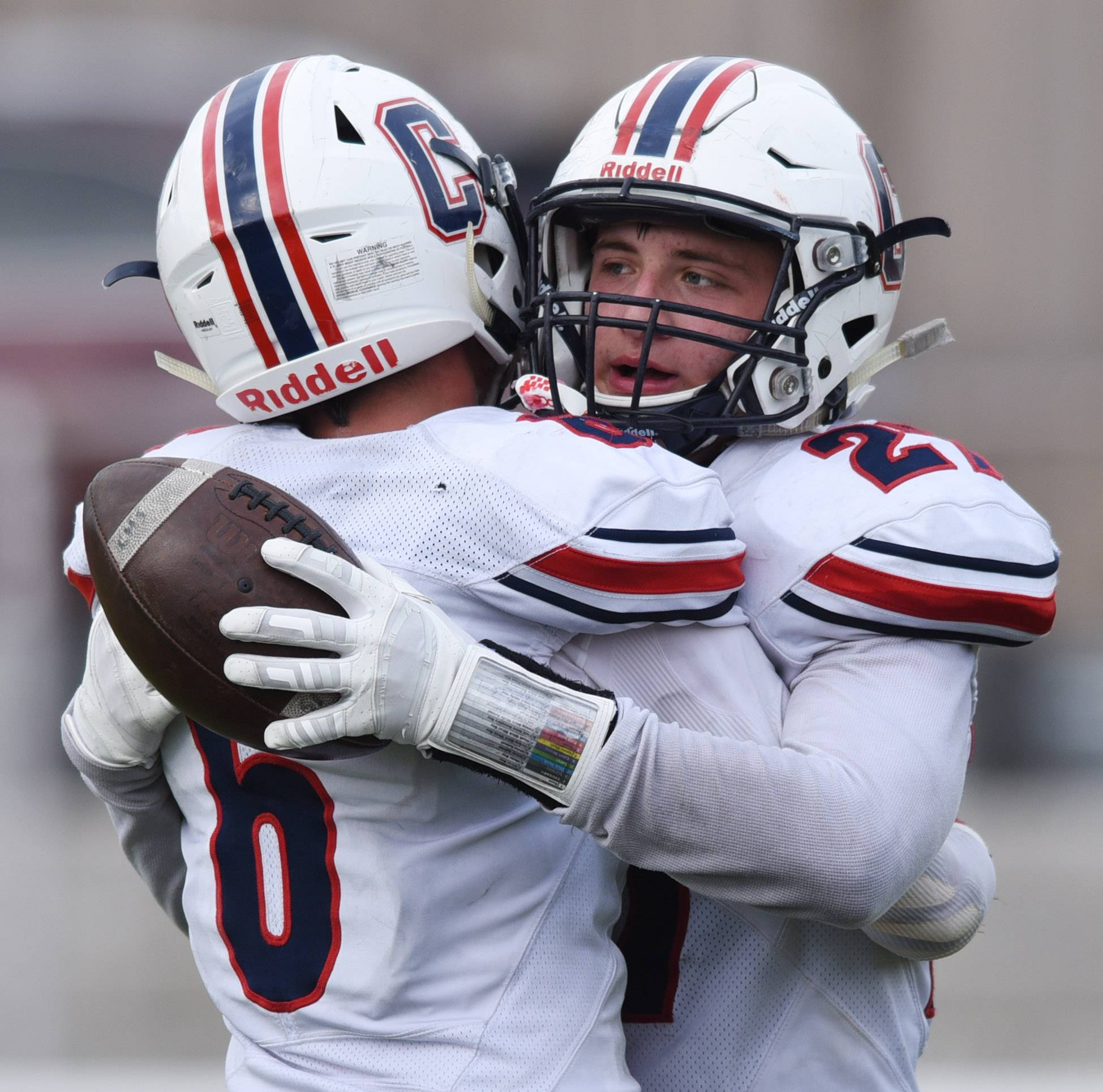 Conant's Anthony Wachal, right, hugs teammate Mason Reiger after scoring a touchdown to make the score 28-14 in favor of Hindale Central with 90 seconds left during Saturday's game in Hinsdale.