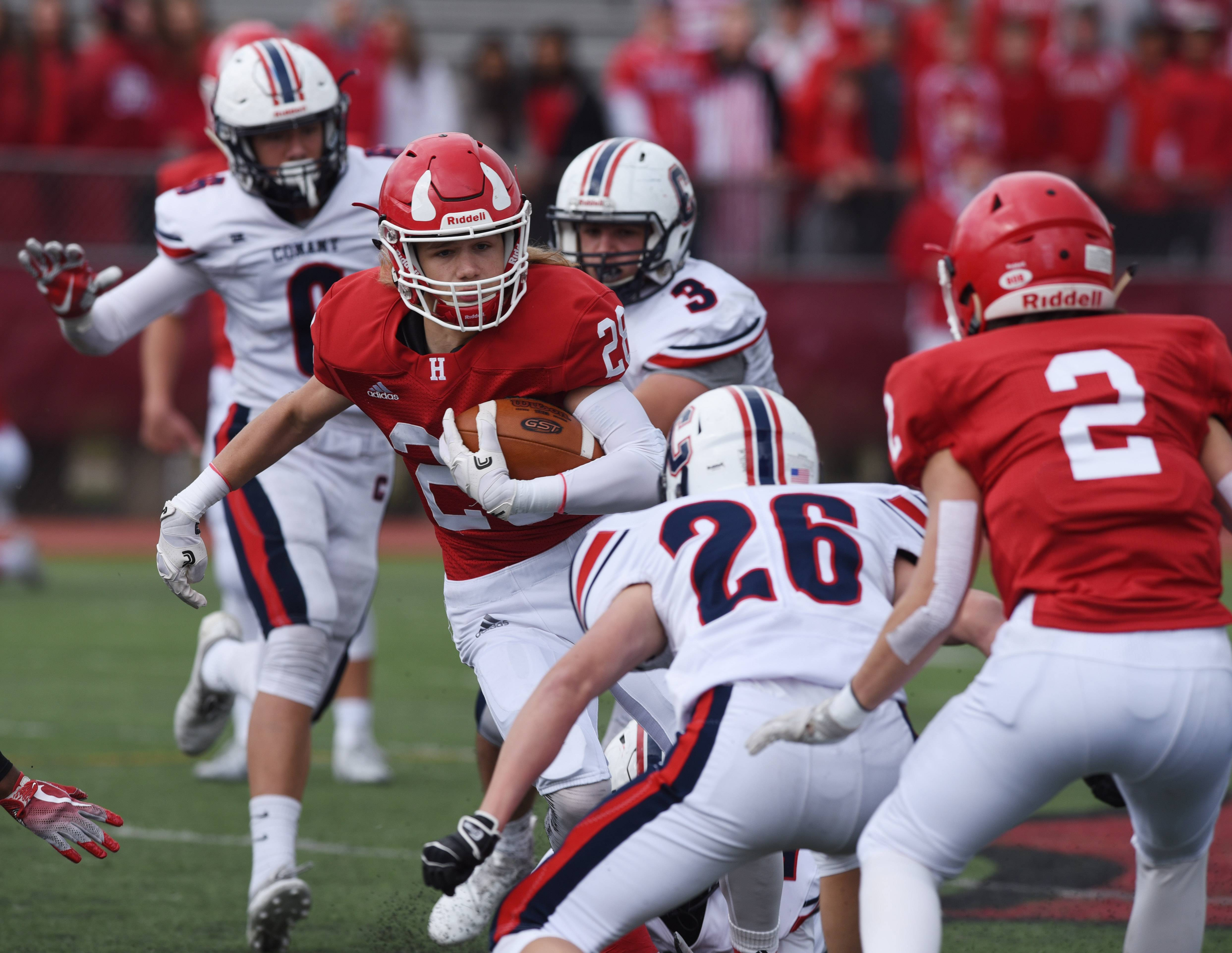 Hinsdale Central ball carrier Mark Skokna runs toward Conant's Zach Valas (26) during Saturday's Class 8A playoff game in Hinsdale.