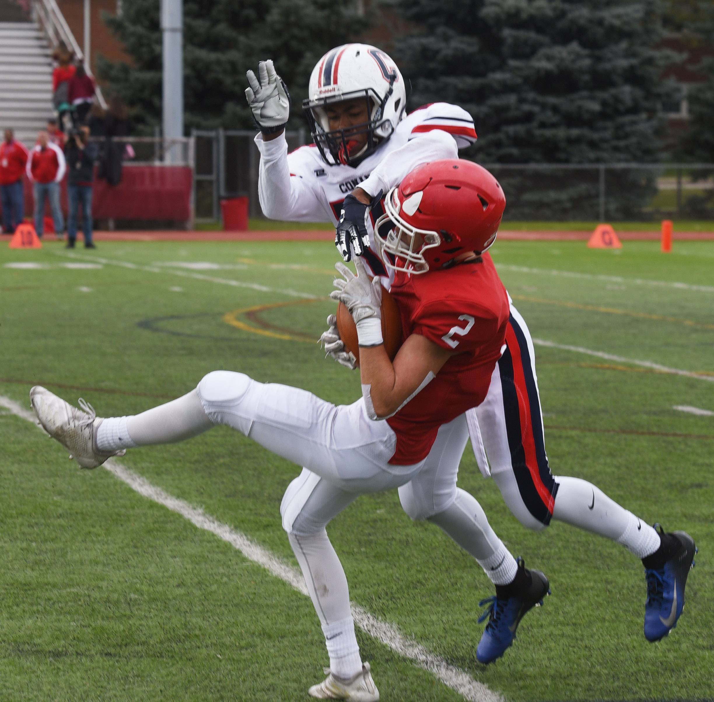 Hinsdale Central's Nick Beaulieu catches a pass as Conant's Ronald Williams defends during Saturday's Class 8A playoff game in Hinsdale.