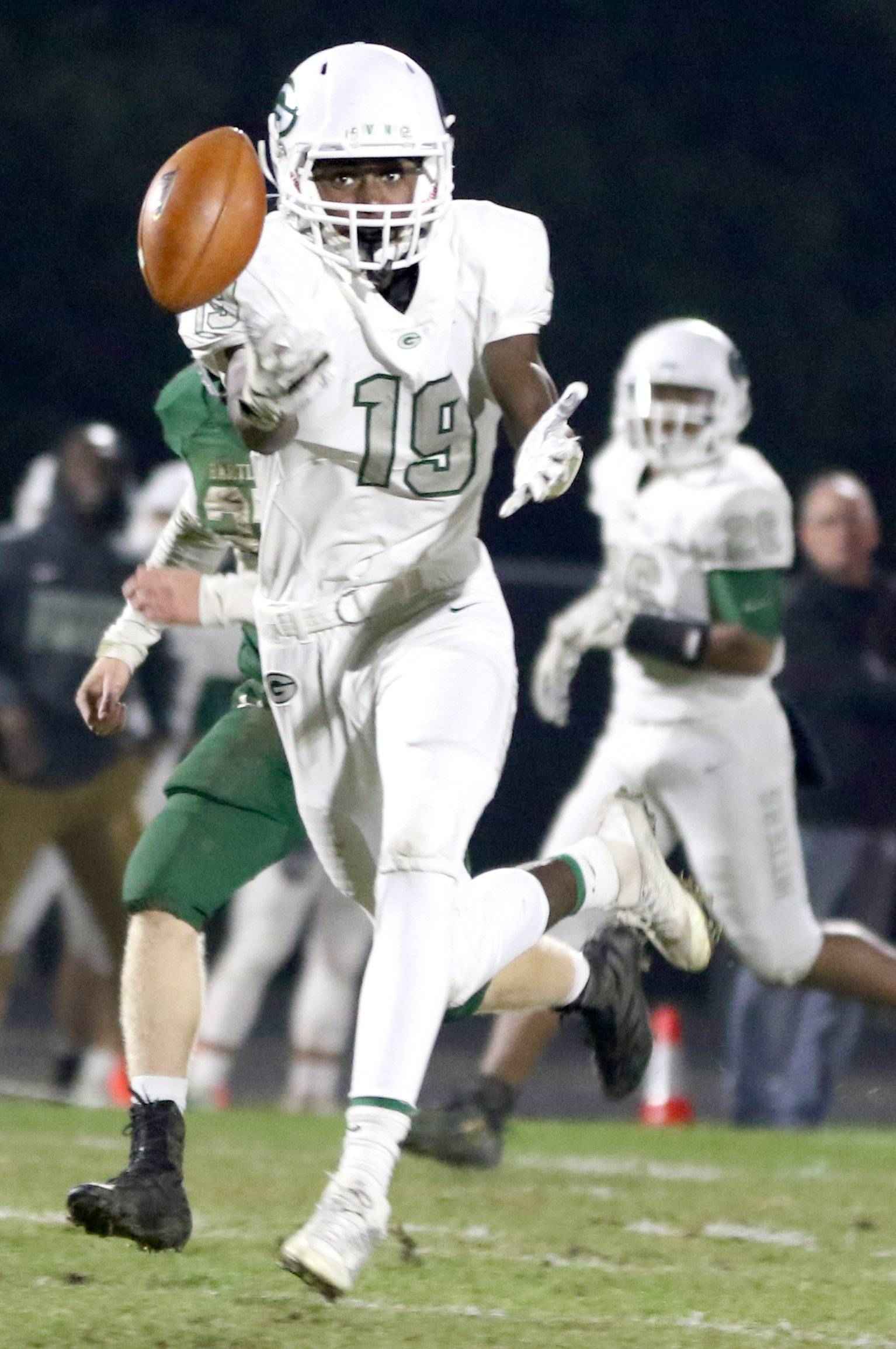 Glenbard West's Corey Williams reels in a pass during first round playoff football action at Bartlett Friday night.