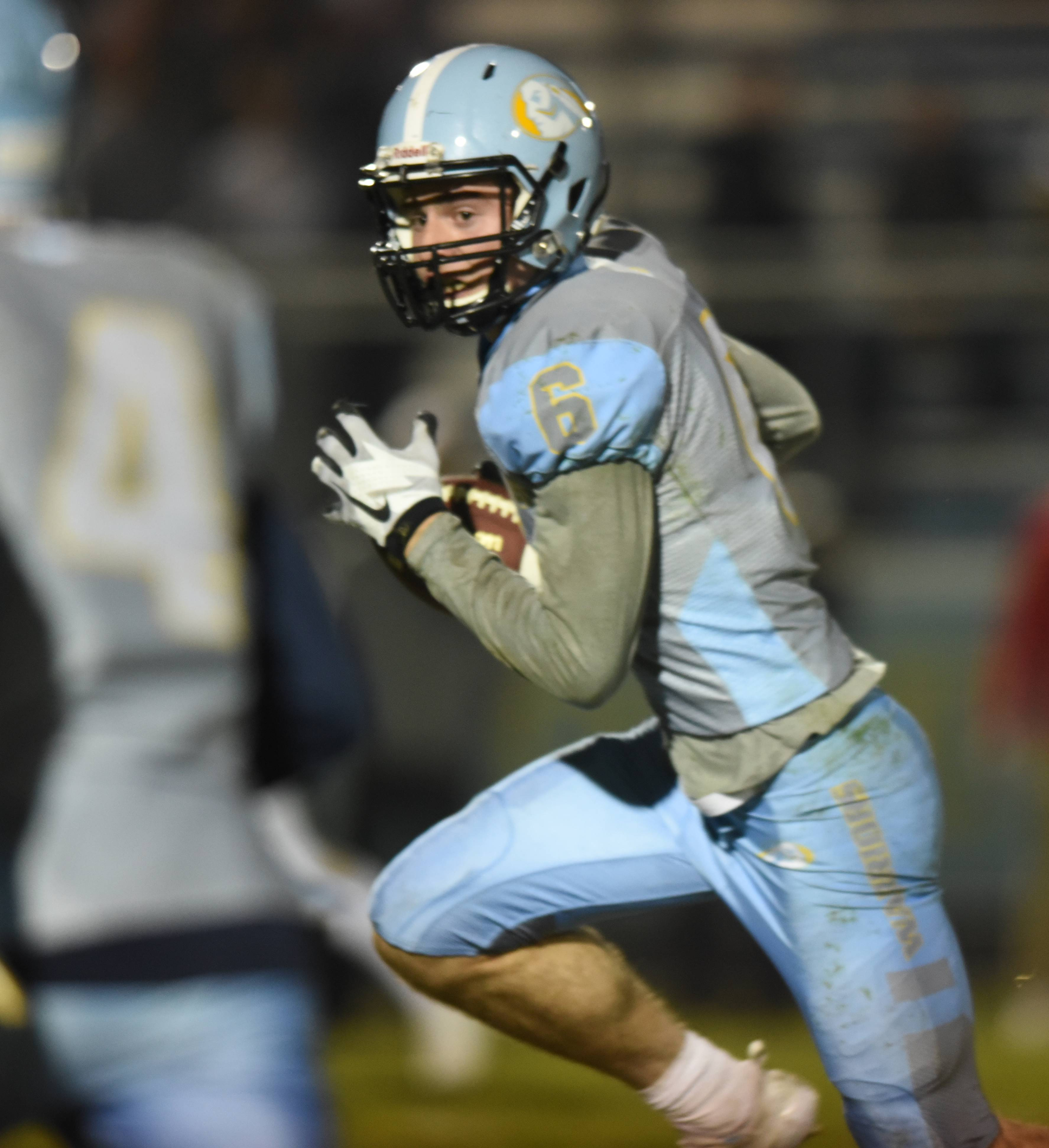 Maine West's Ely Grimmer looks for an opening against Benet last week during the Warriors' 20-18 win in the first round of the Class 7A playoffs. Maine West plays at Willowbrook in the second round on Saturday.