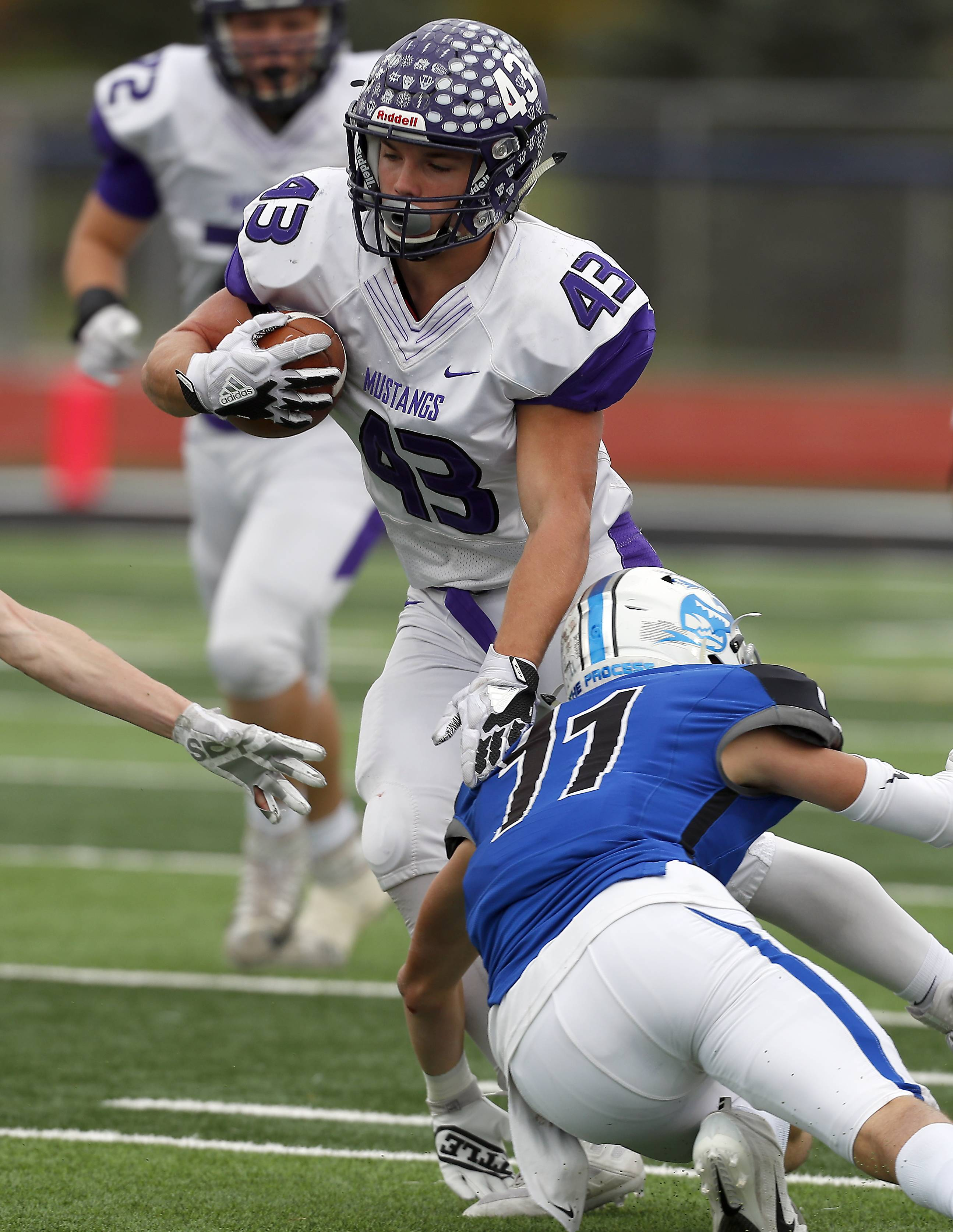 Rolling Meadows' Tymoteusz Szylak (C) (43) slides past St. Charles North's Ethan Romero (21) Saturday during IHSA Class 7A playoff football in St. Charles.
