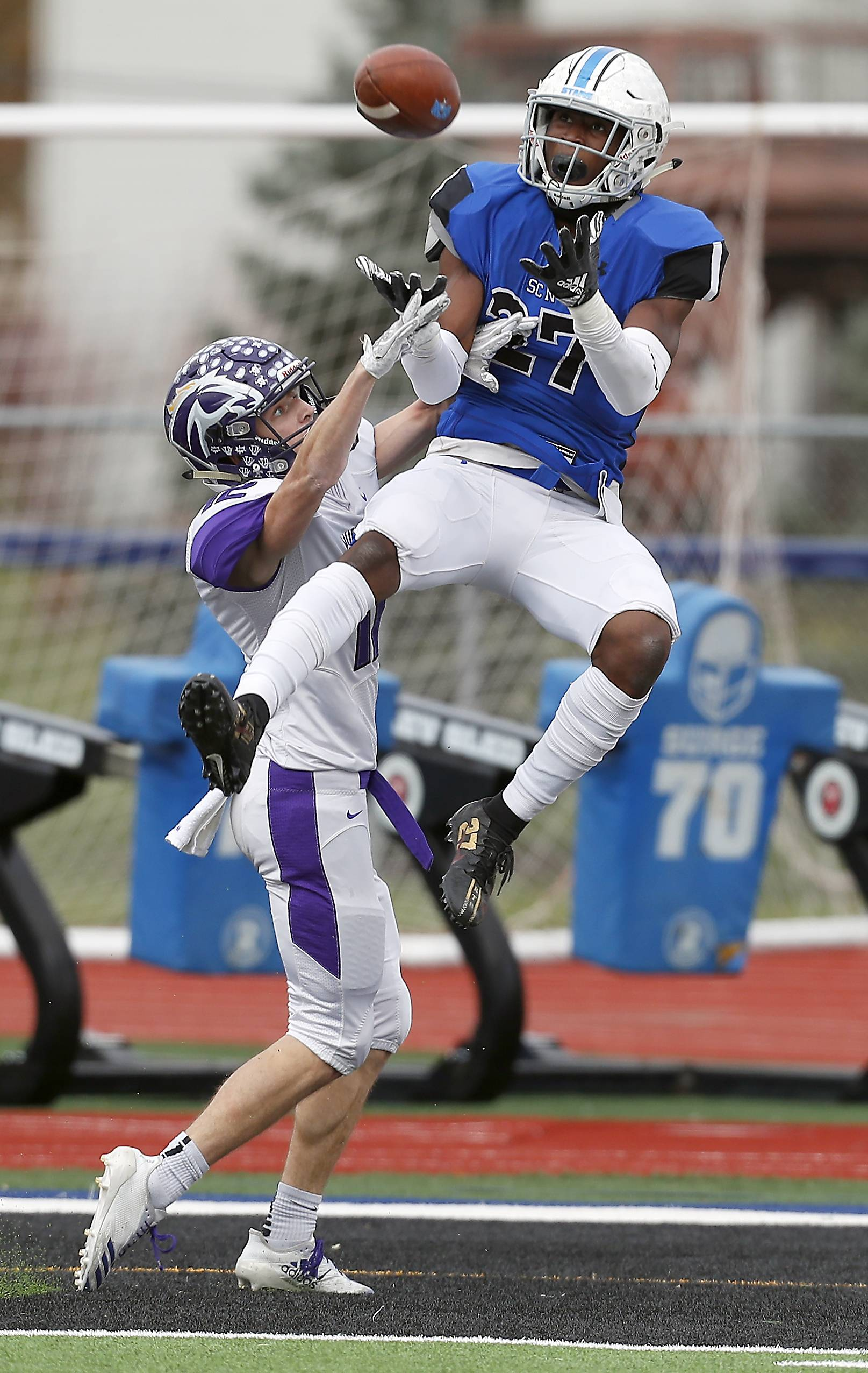 St. Charles North's Tyler Nubin (27) reels in a touchdown pass over Rolling Meadows' Charlie Svoboda (12) Saturday during IHSA Class 7A playoff football in St. Charles.