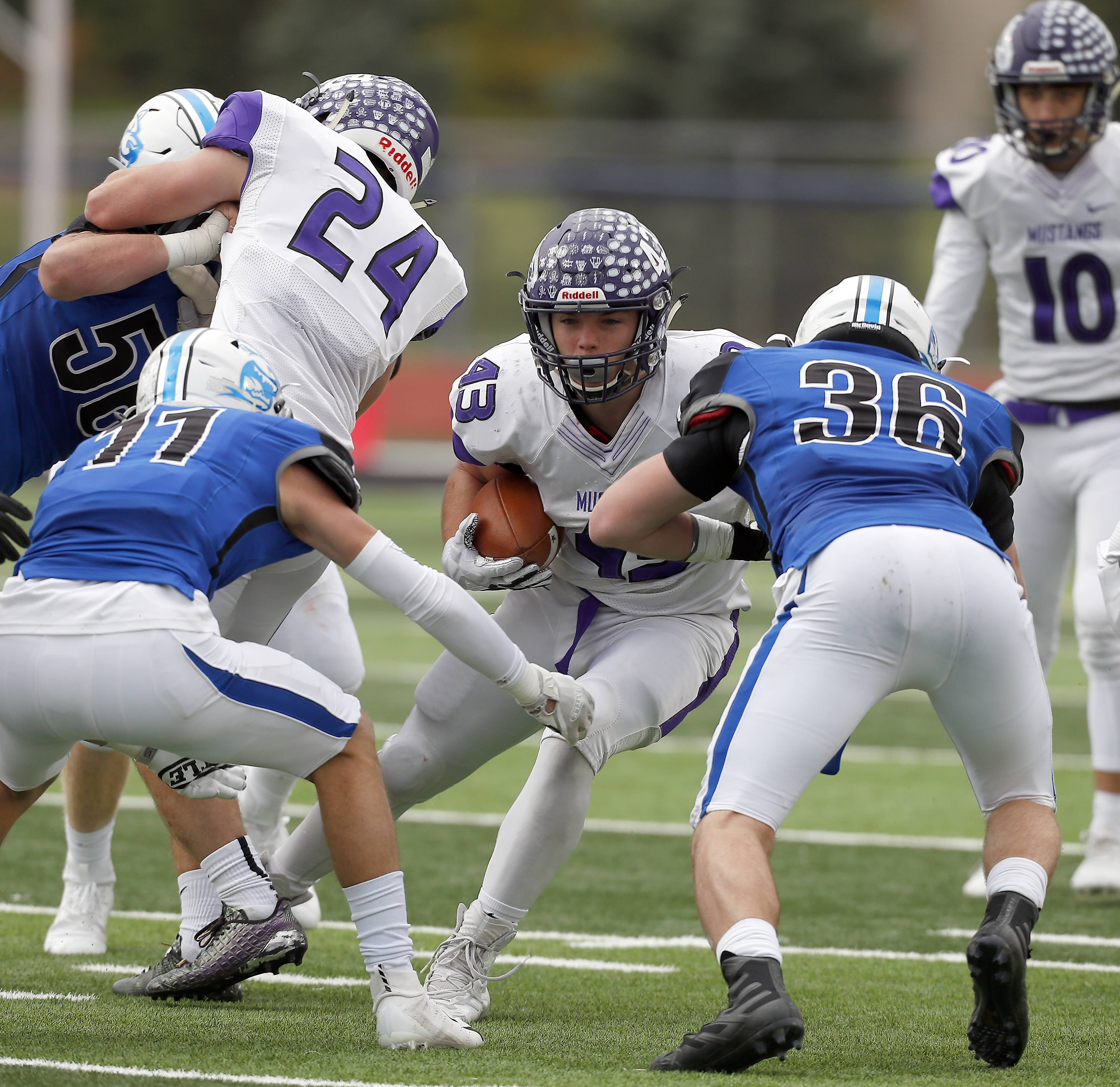 Rolling Meadows' Tymoteusz Szylak (C) (43) moves between St. Charles North's Egon Hein (11) and John Williams, II (36) Saturday during IHSA Class 7A playoff football in St. Charles.