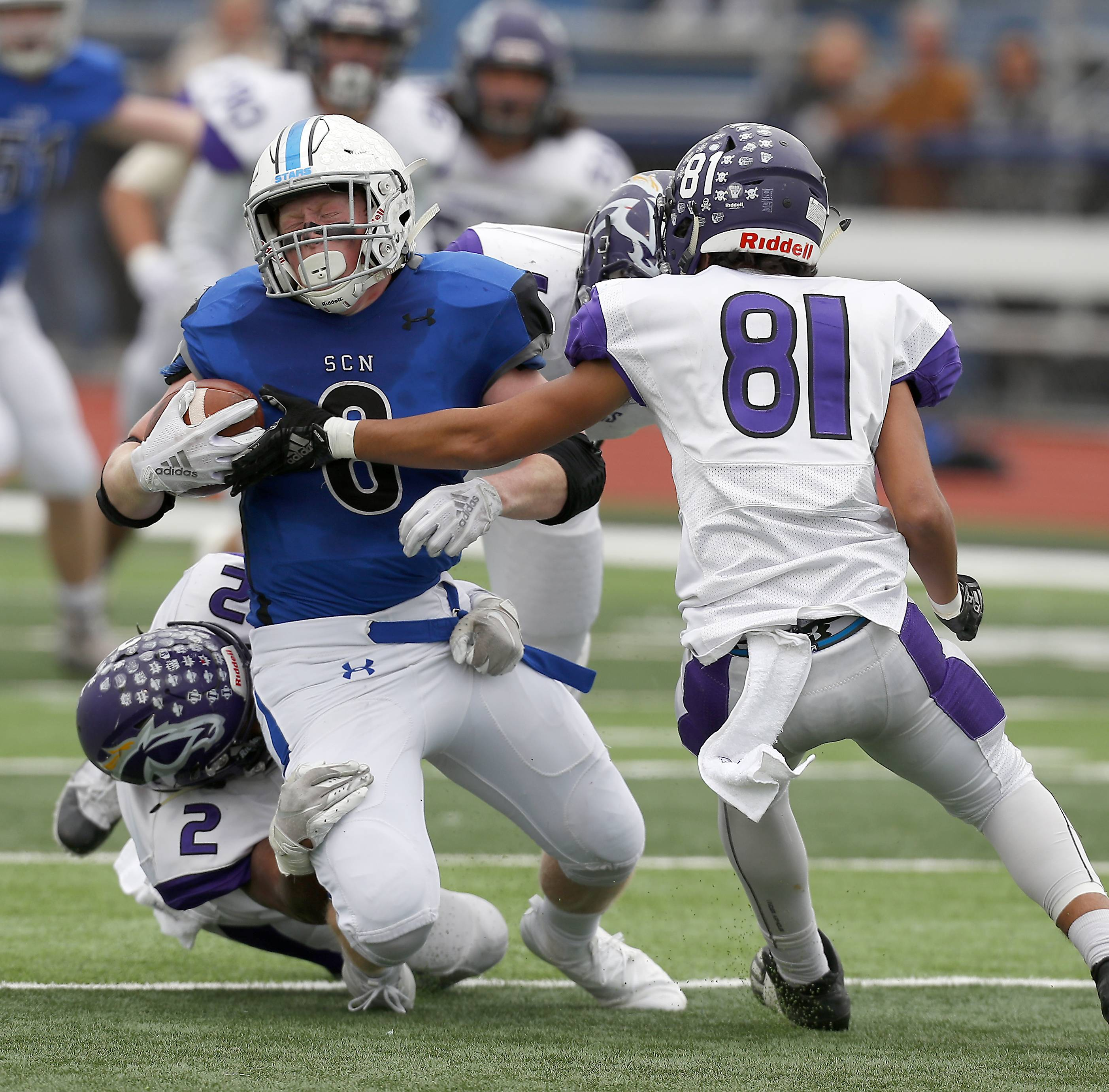 St. Charles North's Ben Furtney (8) slides between Rolling Meadows' Alex Hoffman (8) and Rolling Meadows' TJ Williams (81) Saturday during IHSA Class 7A playoff football in St. Charles.