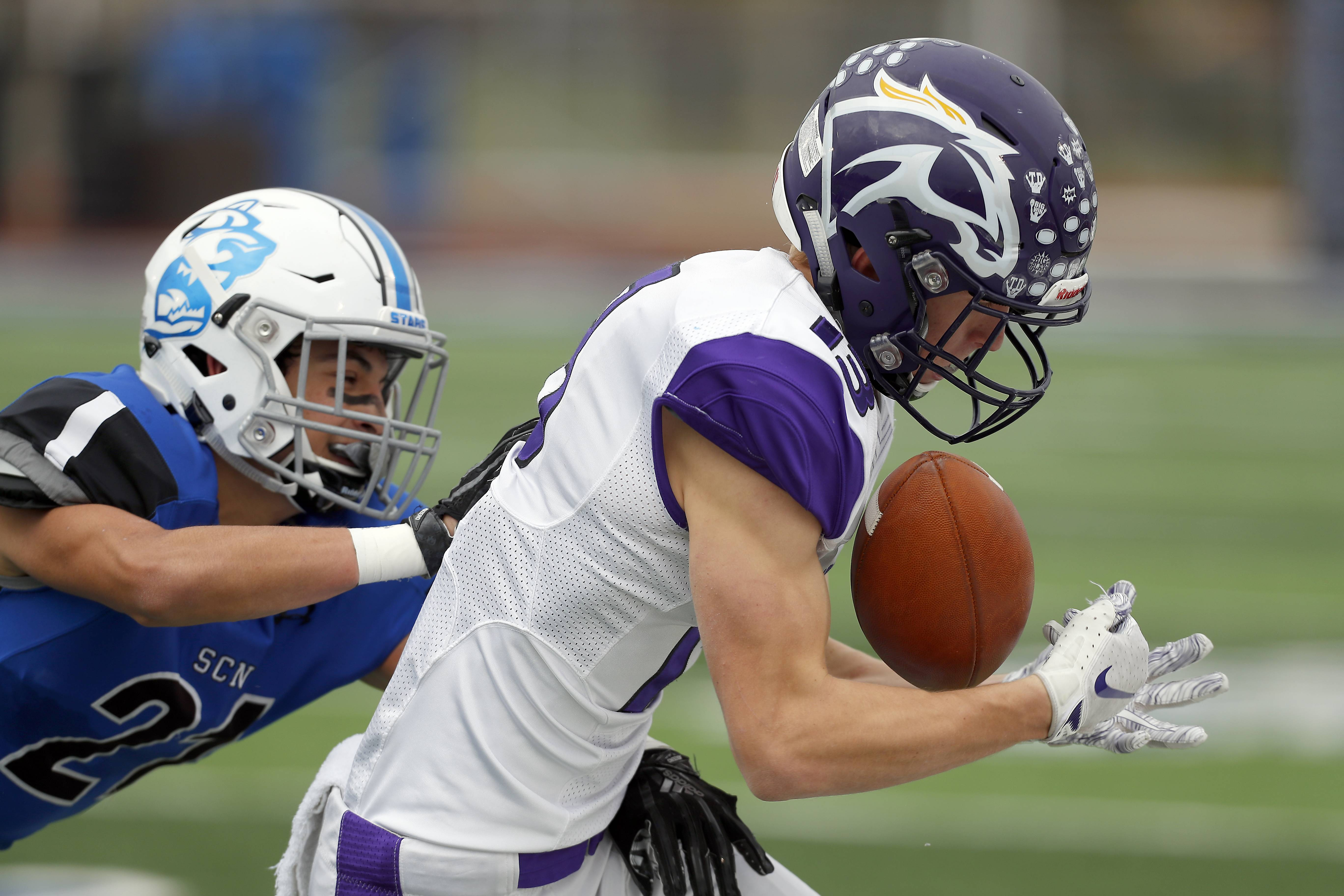 Rolling Meadows' Justin Kretz (13) holds onto a pass as St. Charles North's Ethan Romero (21) tries to stop the play Saturday during IHSA Class 7A playoff football in St. Charles.