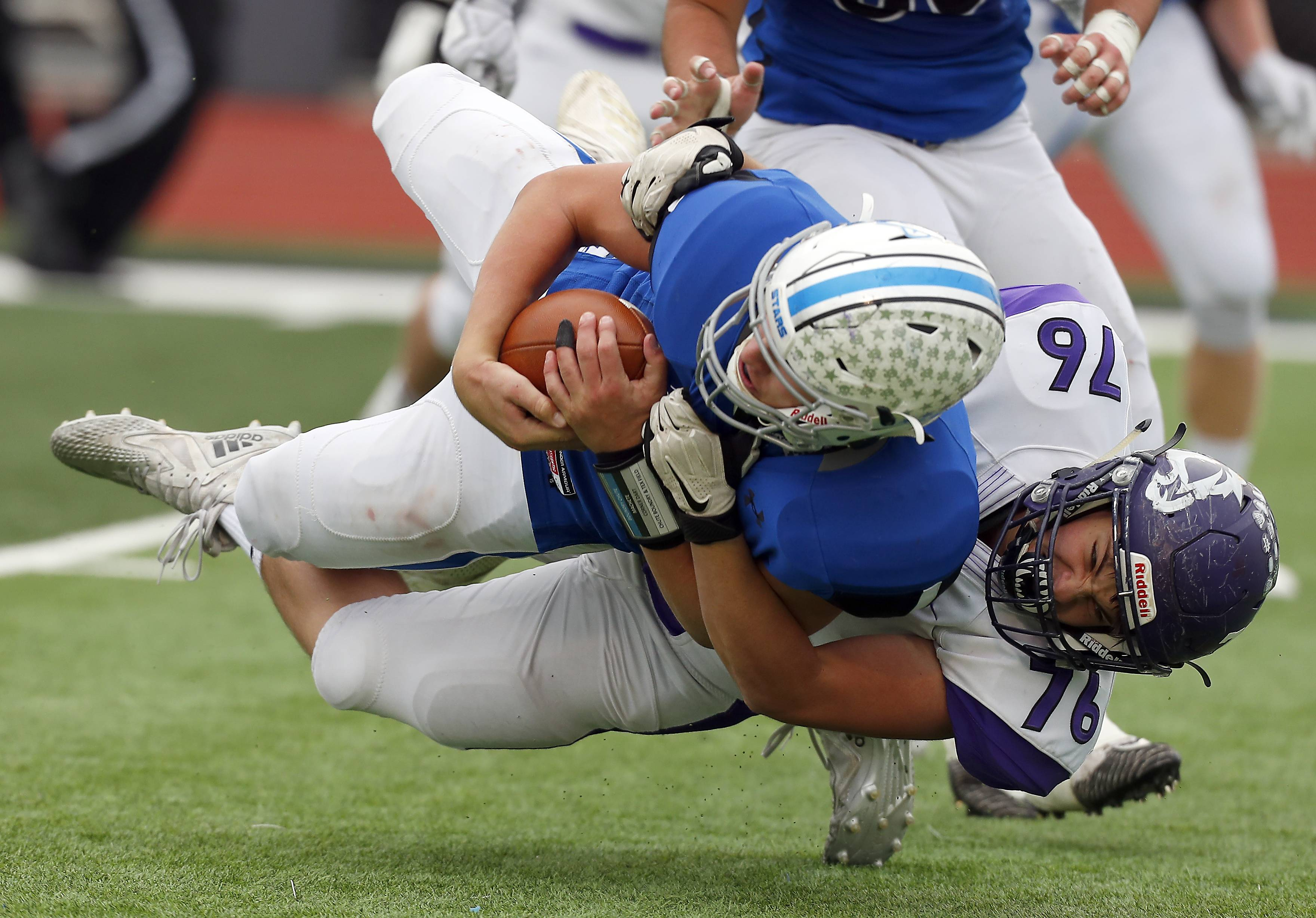 St. Charles North's Billy Durocher (19) is brought down by Rolling Meadows' Thomas Schell (76) after catching a deflection Saturday during IHSA Class 7A playoff football in St. Charles.