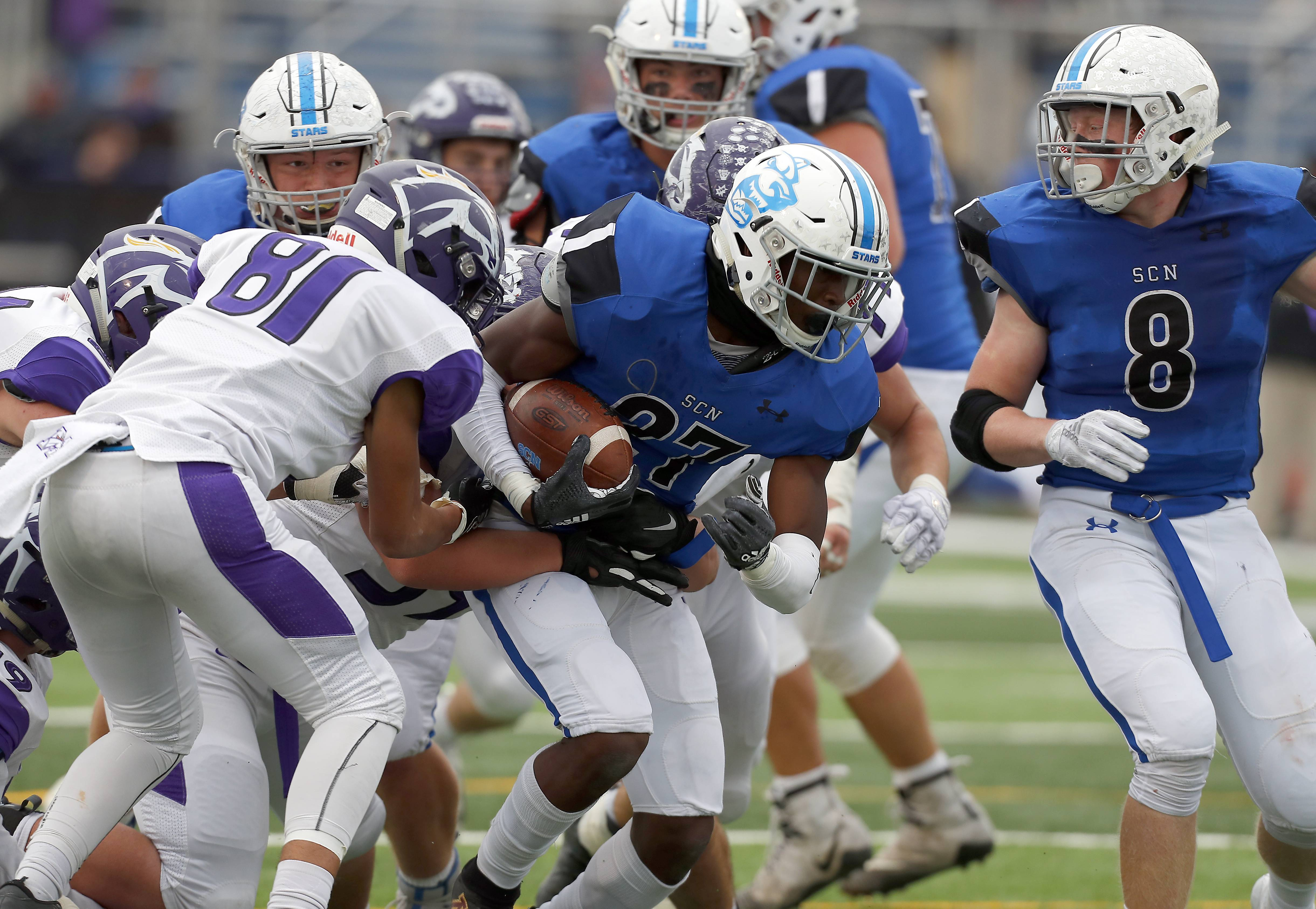 St. Charles North's Tyler Nubin (27) moves upfield with a whole pack of Rolling Meadows players Saturday during IHSA Class 7A playoff football in St. Charles.