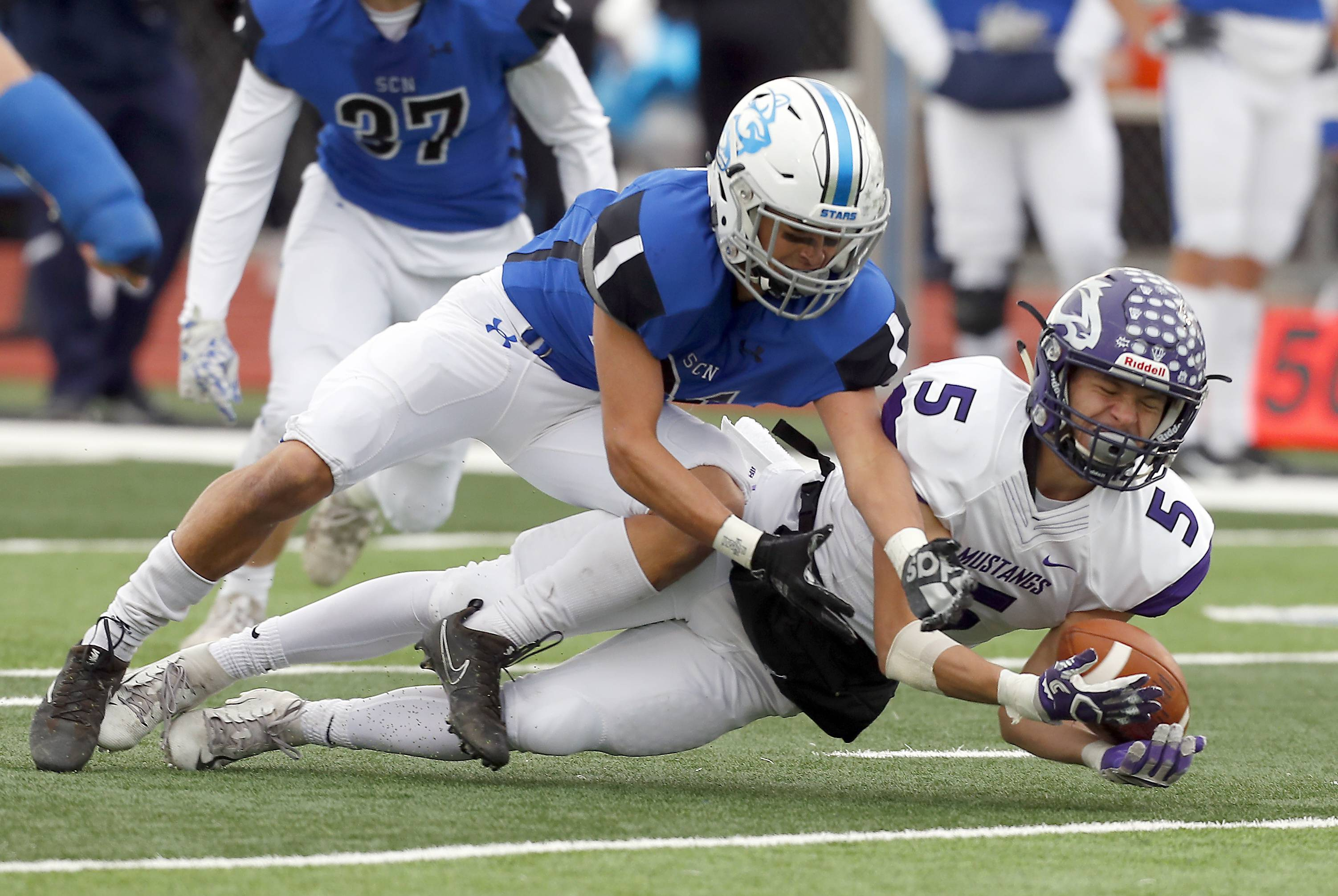 St. Charles North's Ethan Romero (21) tries to stop Rolling Meadows' Kacper Lesniak (5) from completing a catch Saturday during IHSA Class 7A playoff football in St. Charles.