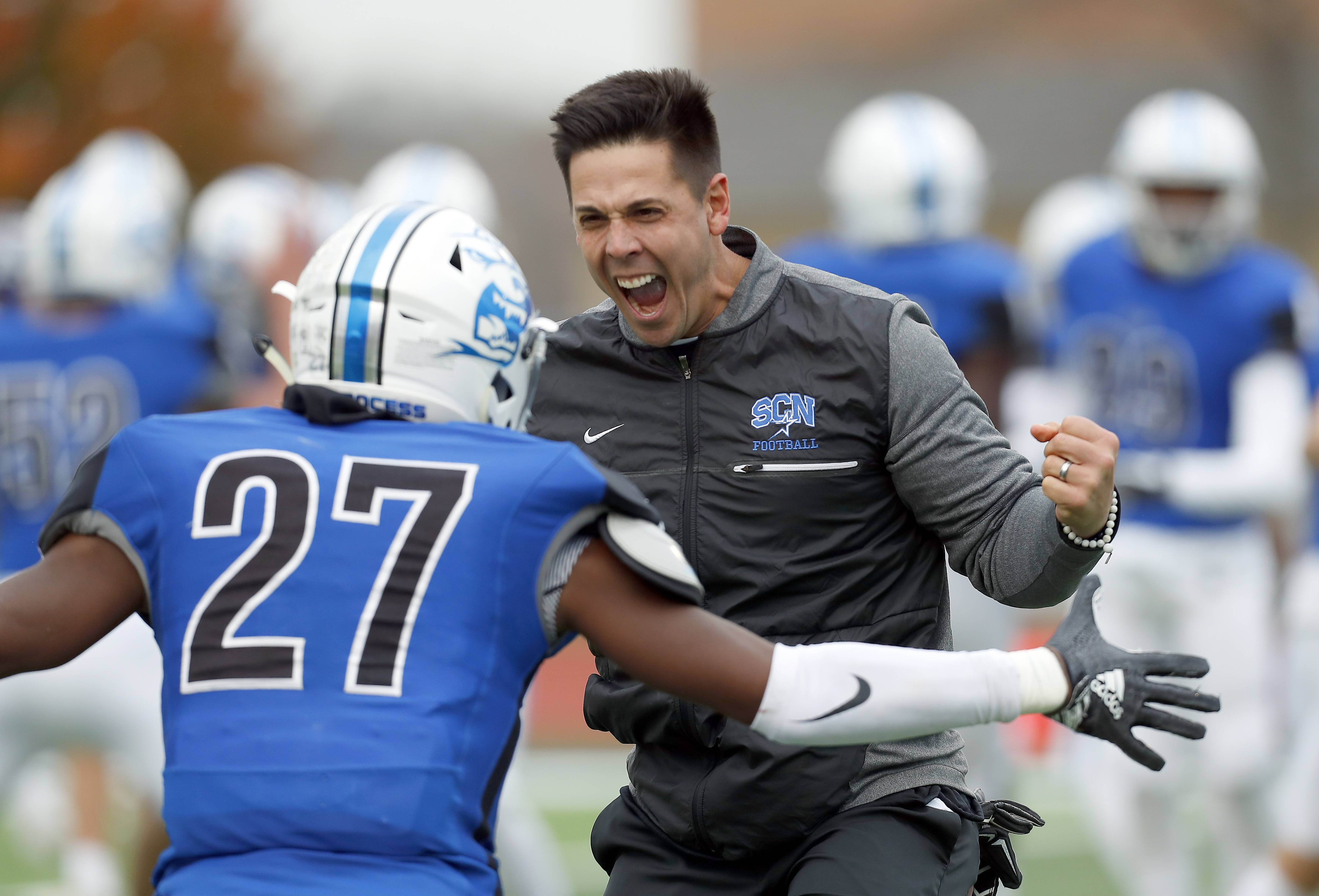 St. Charles North head coach Rob Pomazak and the North Stars' Tyler Nubin (27) celebrate their win Saturday during IHSA Class 7A playoff football in St. Charles.