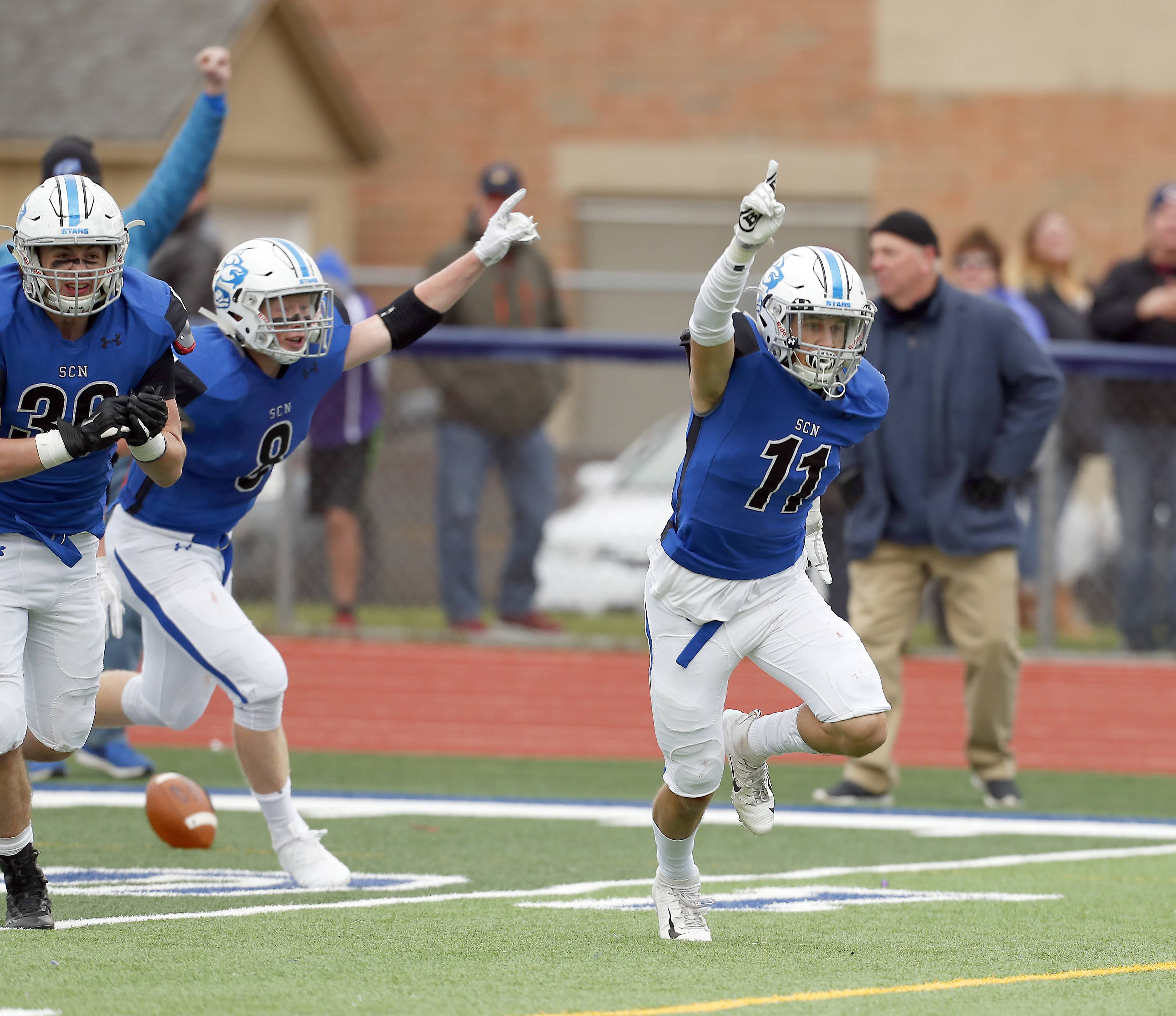 St. Charles North's Egon Hein (11) and his teammates celebrate their win Saturday during IHSA Class 7A playoff football in St. Charles.