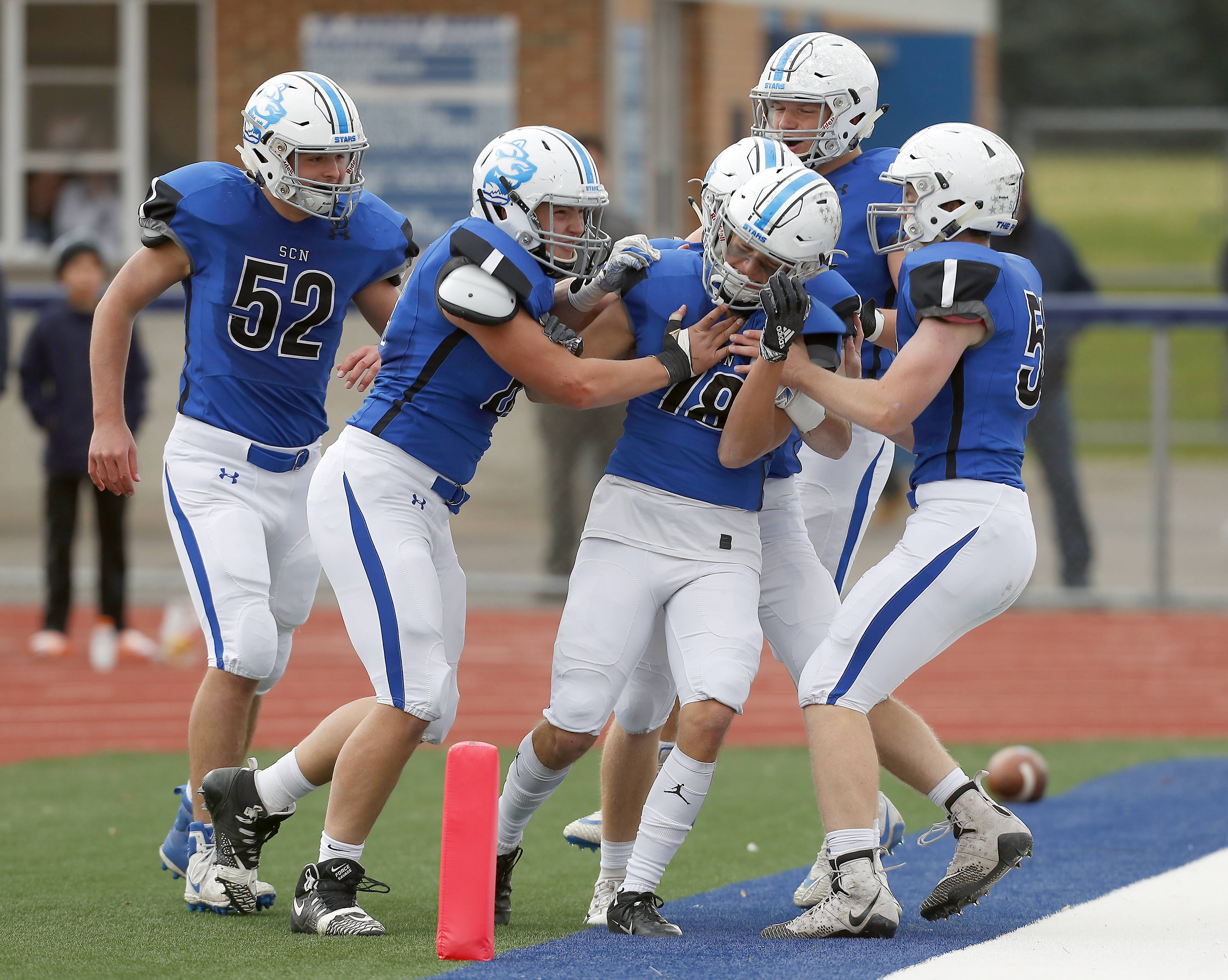 St. Charles North's Alec Kritta (18) is mugged by his teammates Saturday after a touchdown during IHSA Class 7A playoff football in St. Charles.