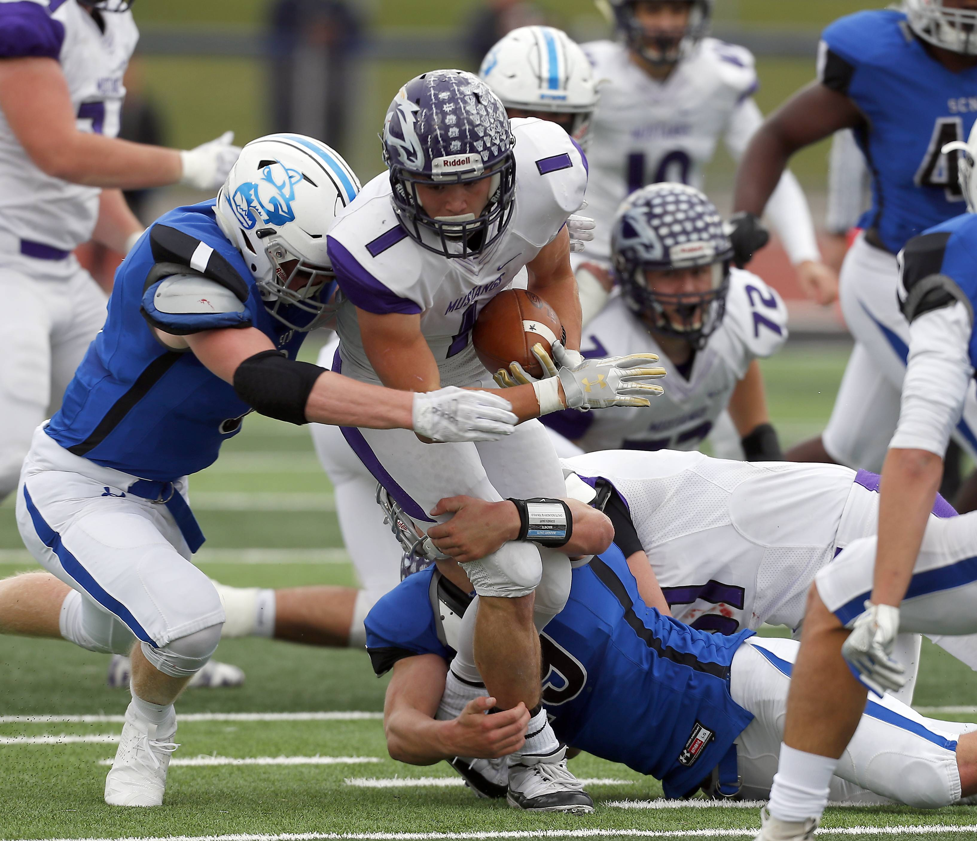 Rolling Meadows' Jace O'Hara (1) is wrapped up by some St. Charles North players Saturday during IHSA Class 7A playoff football in St. Charles.