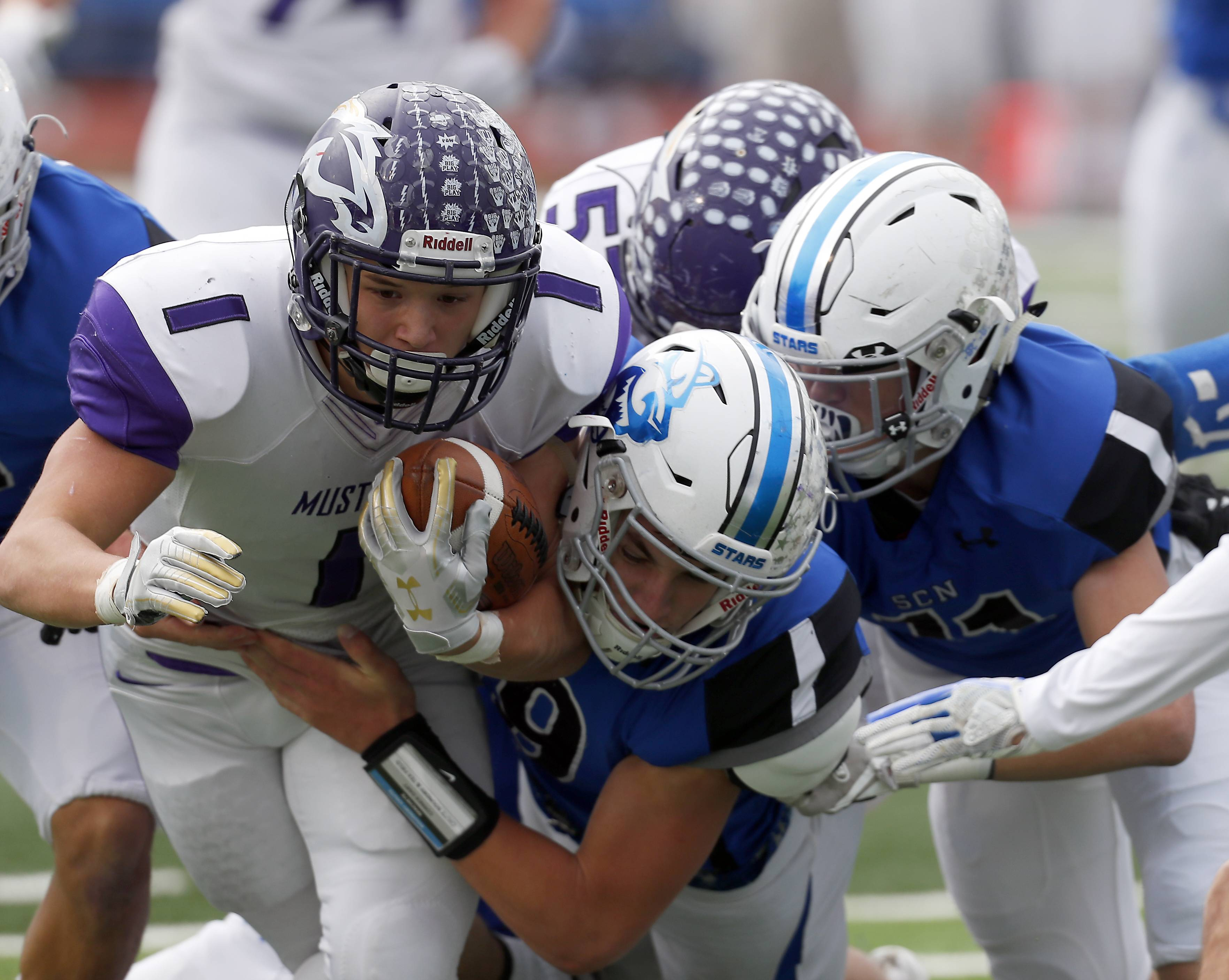 Rolling Meadows' Jace O'Hara (1)j is brought down by a host of St. Charles North players Saturday during IHSA Class 7A playoff football in St. Charles.
