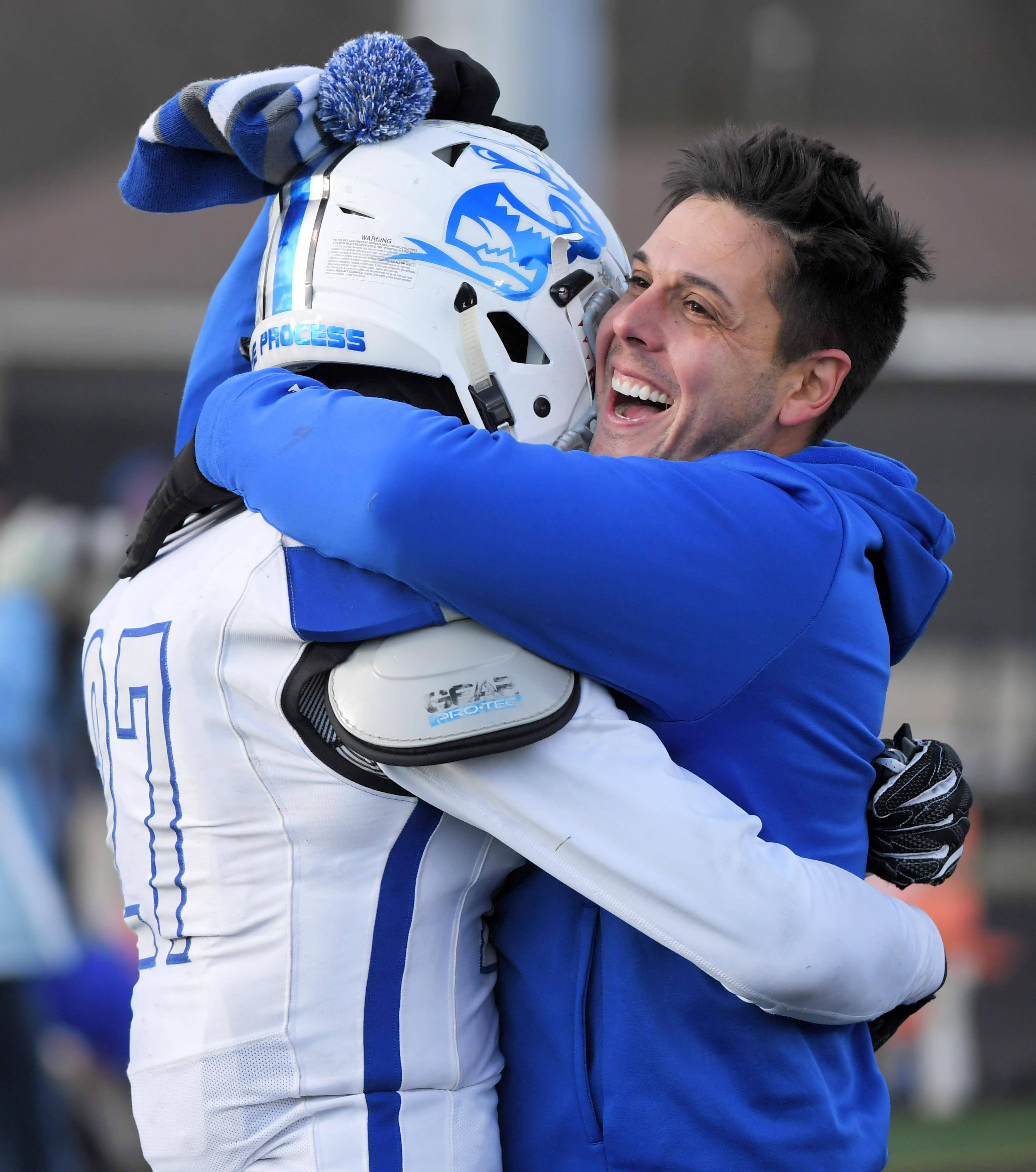 St. Charles North head coach Rob Pomazak hugs Tyler Nubin after the North Stars win against Wheaton Warrenville South Saturday in a quarterfinal playoff football game in Wheaton.