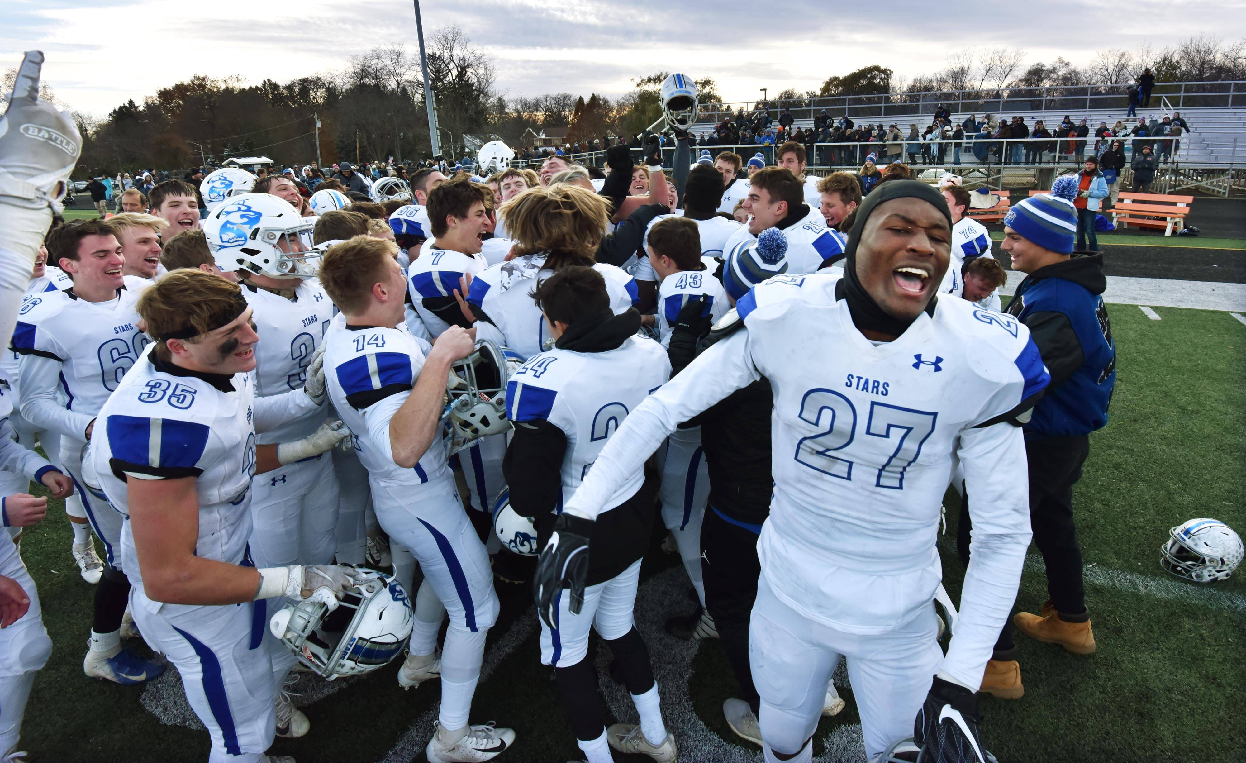 St. Charles North's Tyler Nubin celebrates with teammates after the North Stars defeated Wheaton Warrenville South Saturday in a quarterfinal playoff football game in Wheaton.