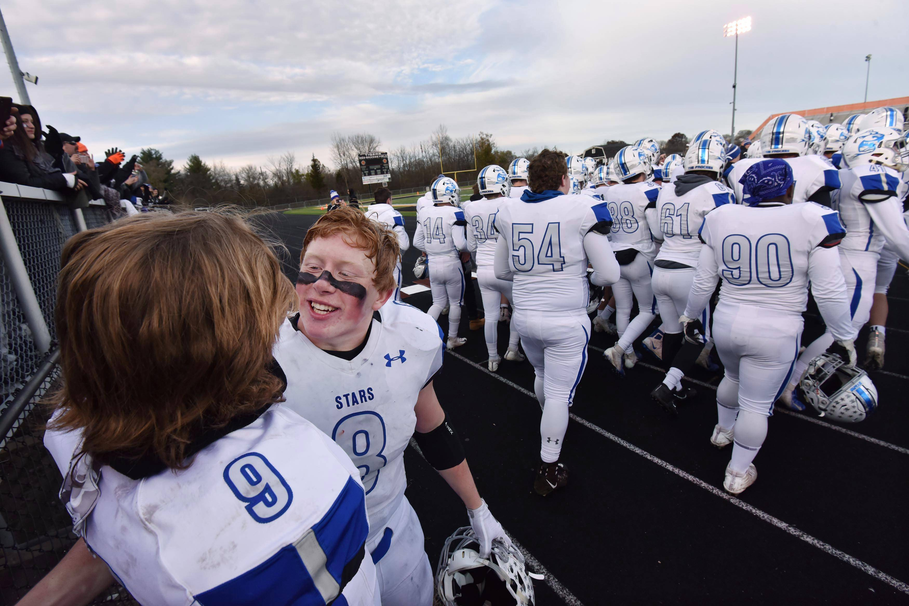 St. Charles North's Ben Furtney and Peyton Brown celebrate the North Stars win against Wheaton Warrenville South Saturday in a quarterfinal playoff football game in Wheaton.