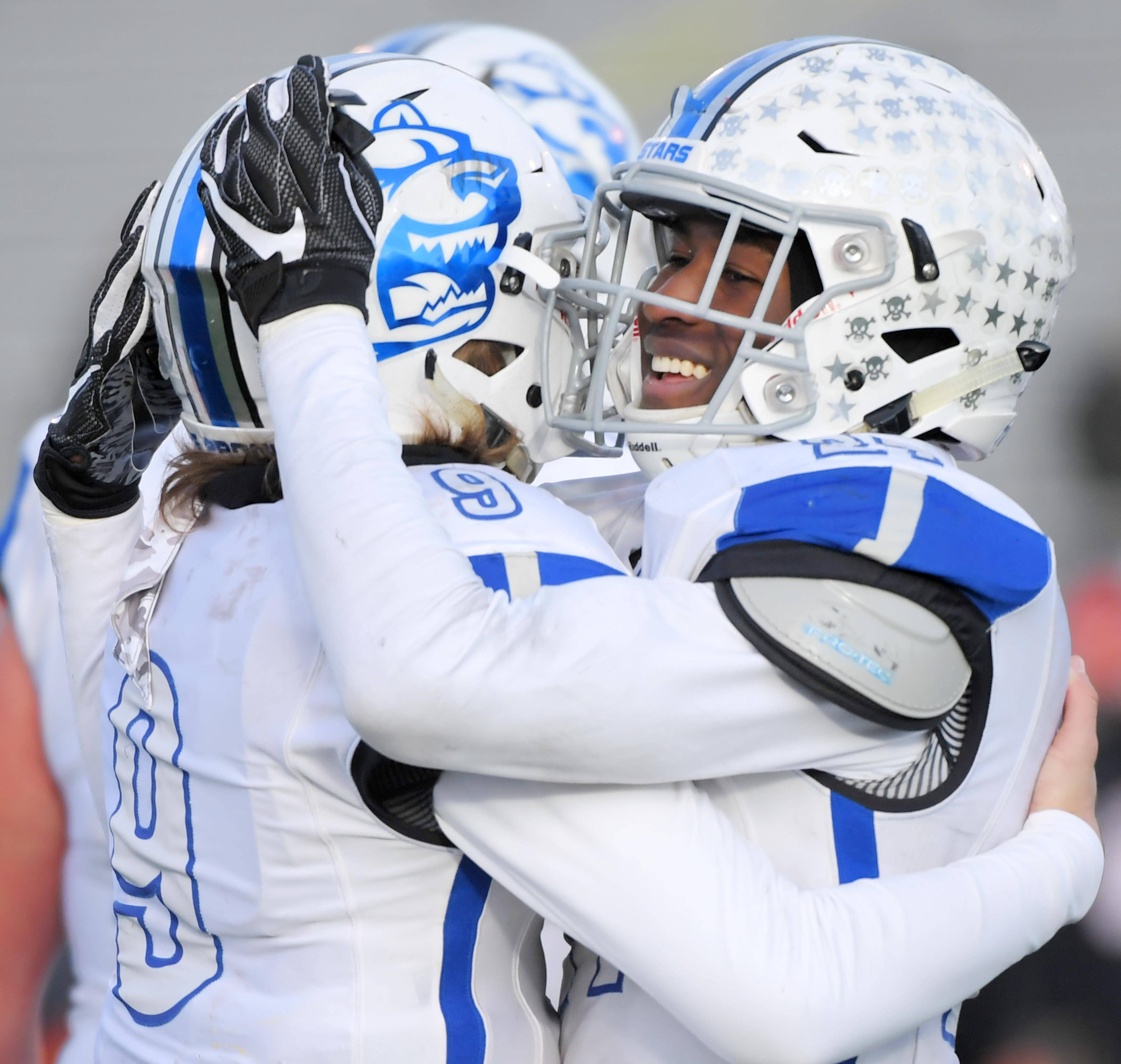 St. Charles North's Tyler Nubin hugs quarterback Peyton Brown after the North Stars win against Wheaton Warrenville South Saturday in a quarterfinal playoff football game in Wheaton.
