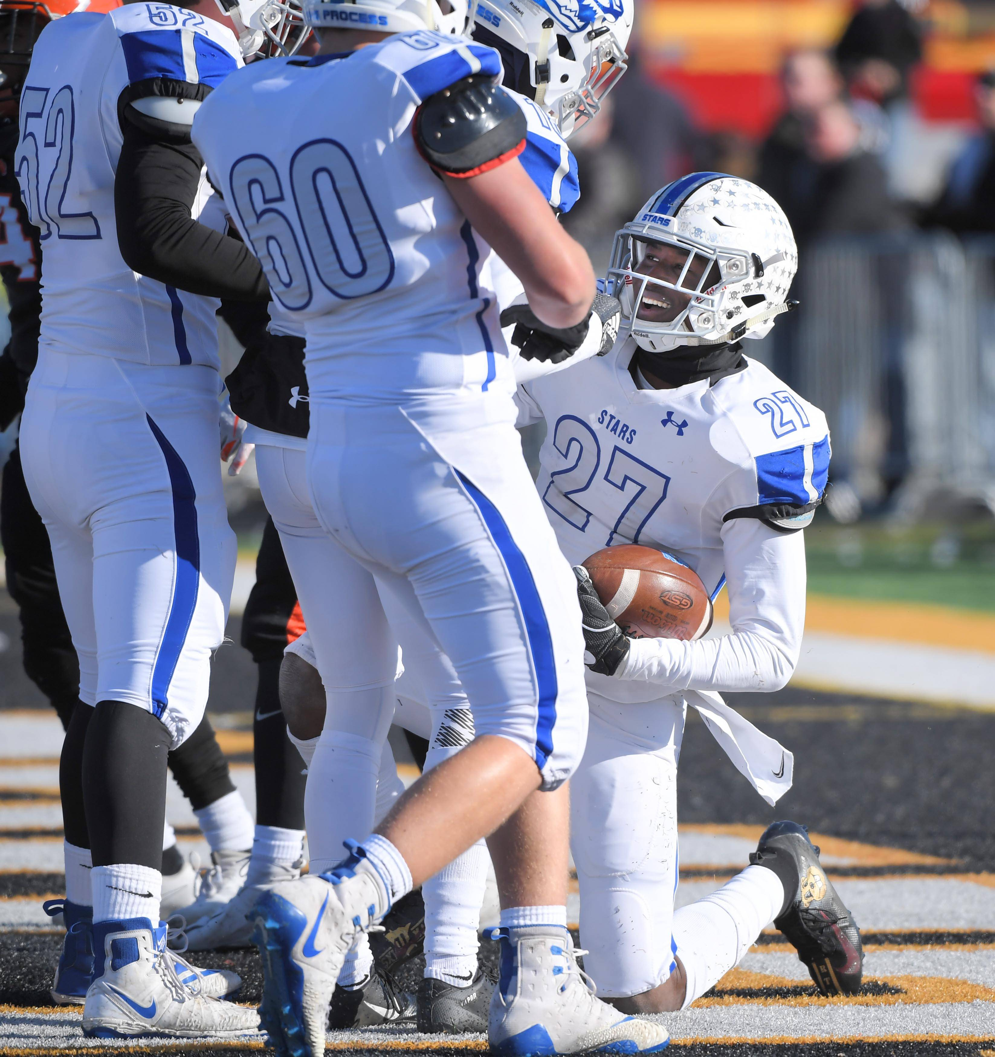 St. Charles North's Tyler Nubin is met by teammates in the end zone after his first-quarter touchdown catch against Wheaton Warrenville South Saturday in a quarterfinal playoff football game in Wheaton.