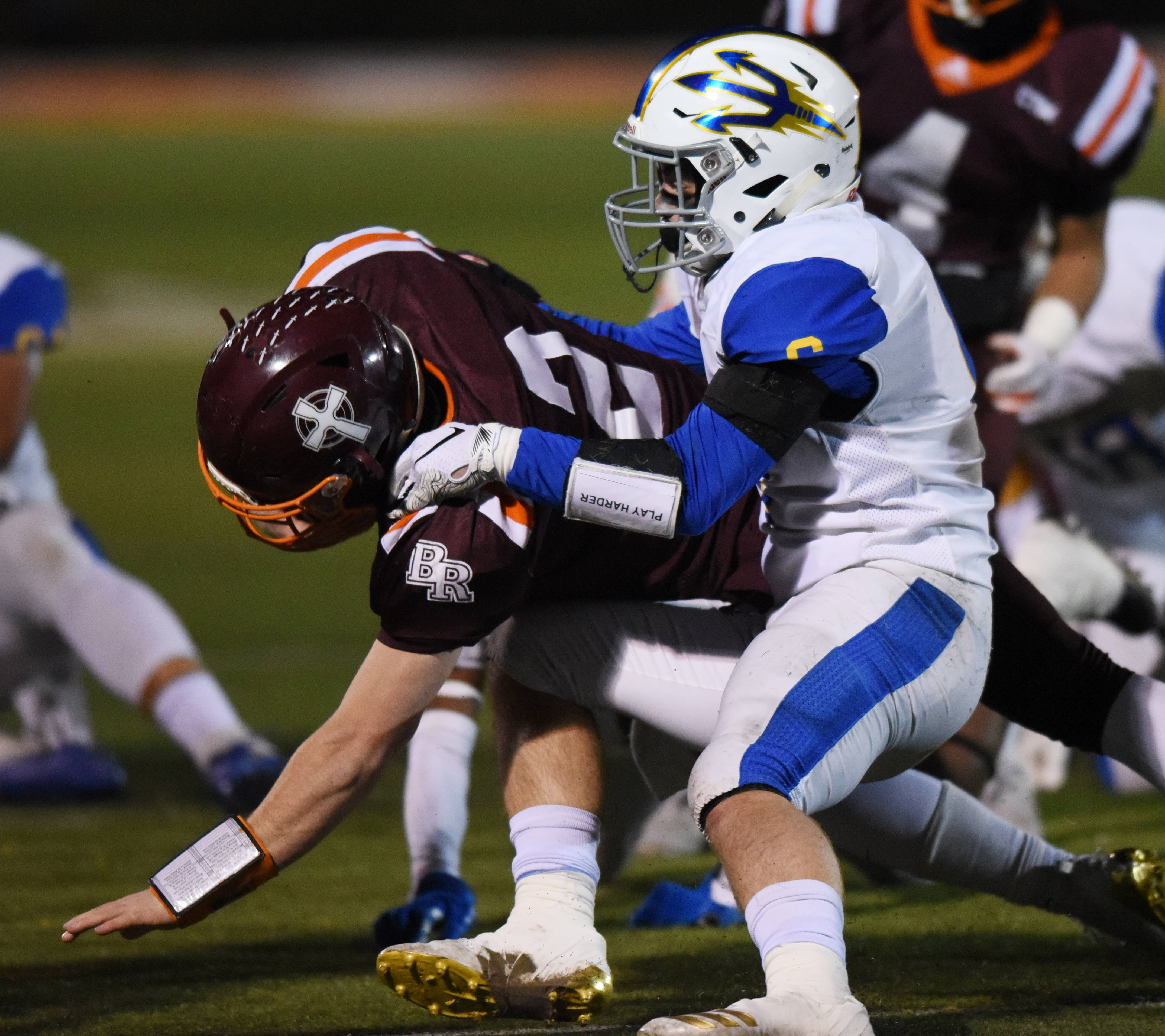 Warren's Brian Mohry, right, tackles Brother Rice quarterback John Bean during the Class 8A state quarterfinal in Chicago Saturday.