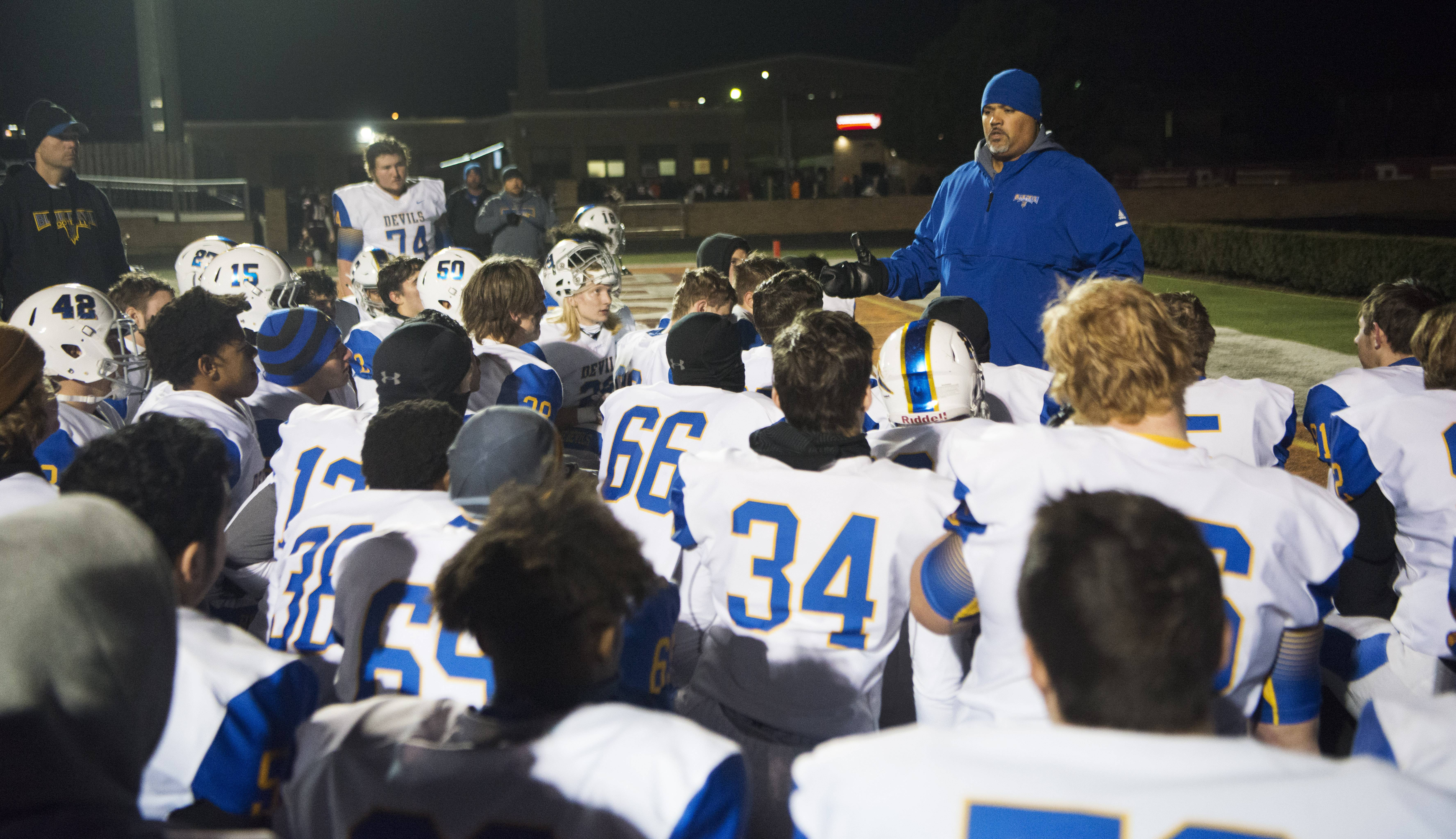 Warren head coach Brian McNulty talks to his team in the end zone following the Blue Devils' 20-0 loss to Brother Rice during the Class 8A state quarterfinal in Chicago Saturday.