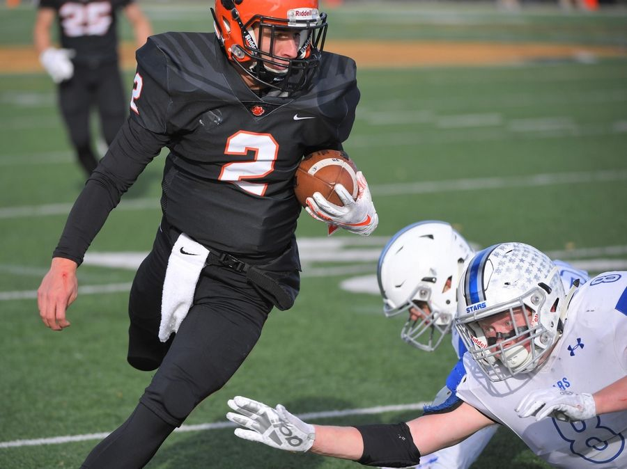 Wheaton Warrenville South's Noah Henkel tries to find a way as St. Charles North's Ben Furtney tries to stop him late in the first half Saturday in a quarterfinal playoff football game in Wheaton.