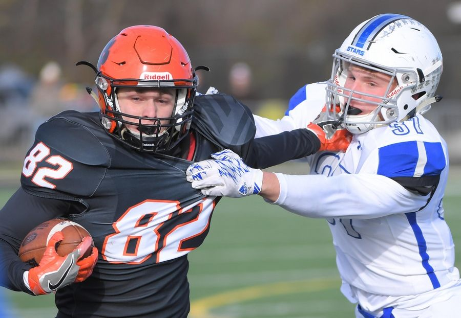 Wheaton Warrenville South's Jack Olsen tries to get around St. Charles North's Ryan Thiesse in the second quarter Saturday in a quarterfinal playoff football game in Wheaton.