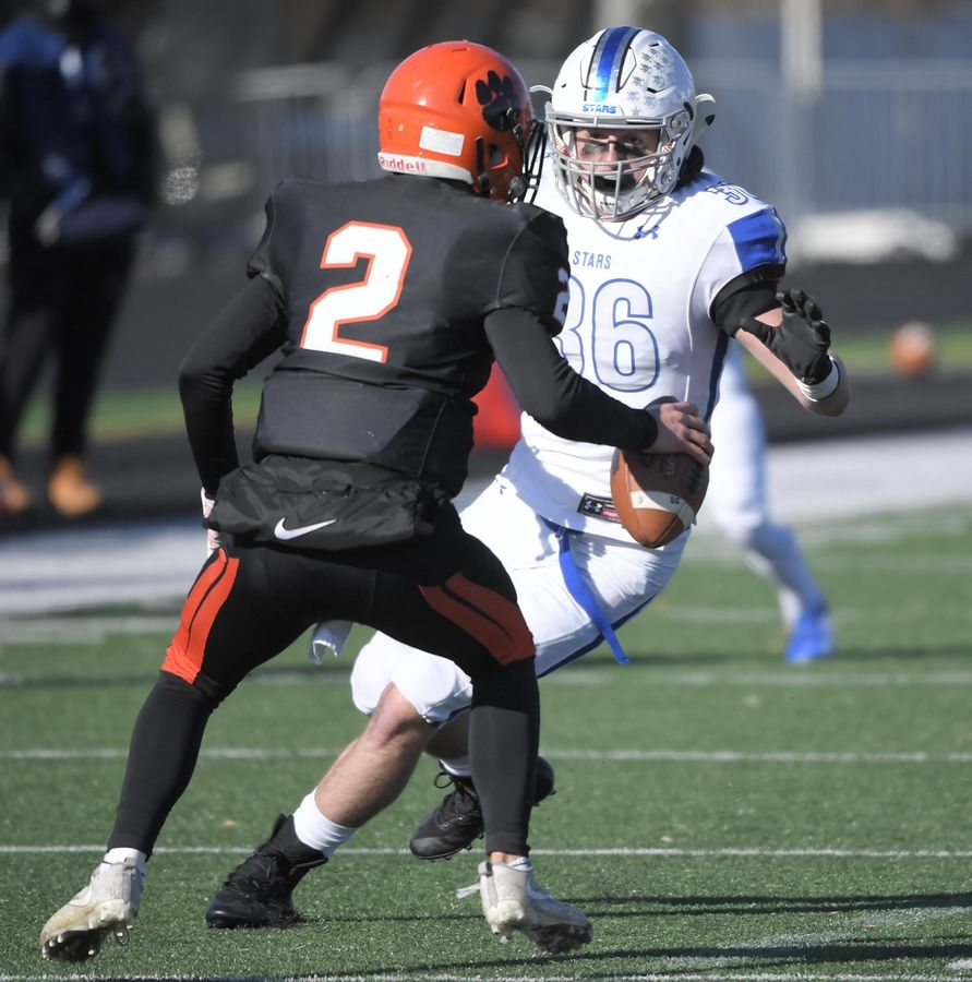 St. Charles North's John Williams, II contains Wheaton Warrenville South quarterback Noah Henkel Saturday in a quarterfinal playoff football game in Wheaton.
