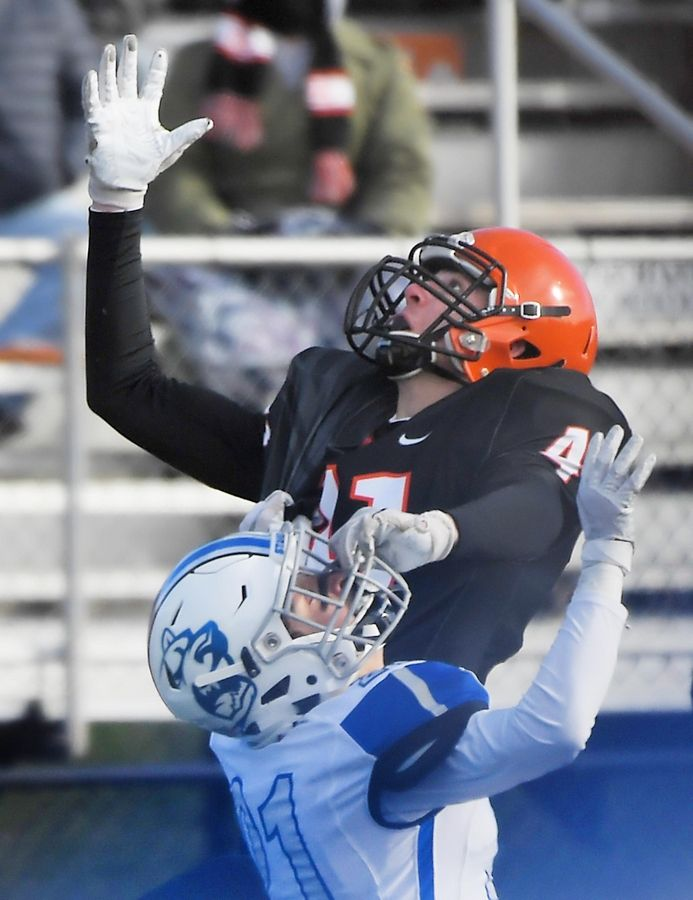 Wheaton Warrenville South's Tyler Fawcett grabs the facemark of St. Charles North's Ethan Romero as he makes a one-handed catch for a first down in the second quarter Saturday in a quarterfinal playoff football game in Wheaton. A penalty was called on Romero.