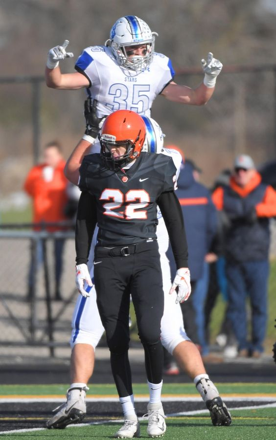 St. Charles North's Nicholas DeMarco is lifted by teammate Alex Westendorf after his second quarter touchdown run against Wheaton Warrenville South Saturday in a quarterfinal playoff football game in Wheaton.