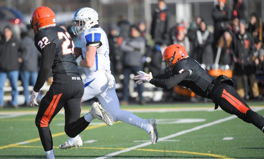 Wheaton Warrenville South's Lauden Dome dives but can't stop St. Charles North's Nicholas DeMarco from a long touchdown run Saturday in a quarterfinal playoff football game in Wheaton.