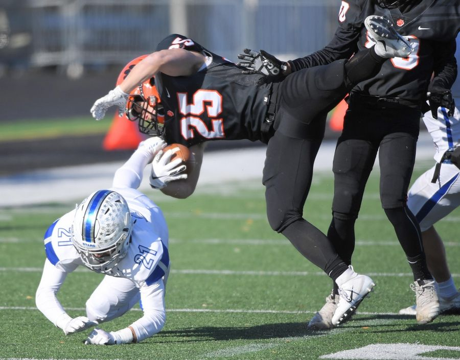 Wheaton Warrenville South's Jake Arthurs is stopped by St. Charles North's Ethan Romero Saturday in a quarterfinal playoff football game in Wheaton.