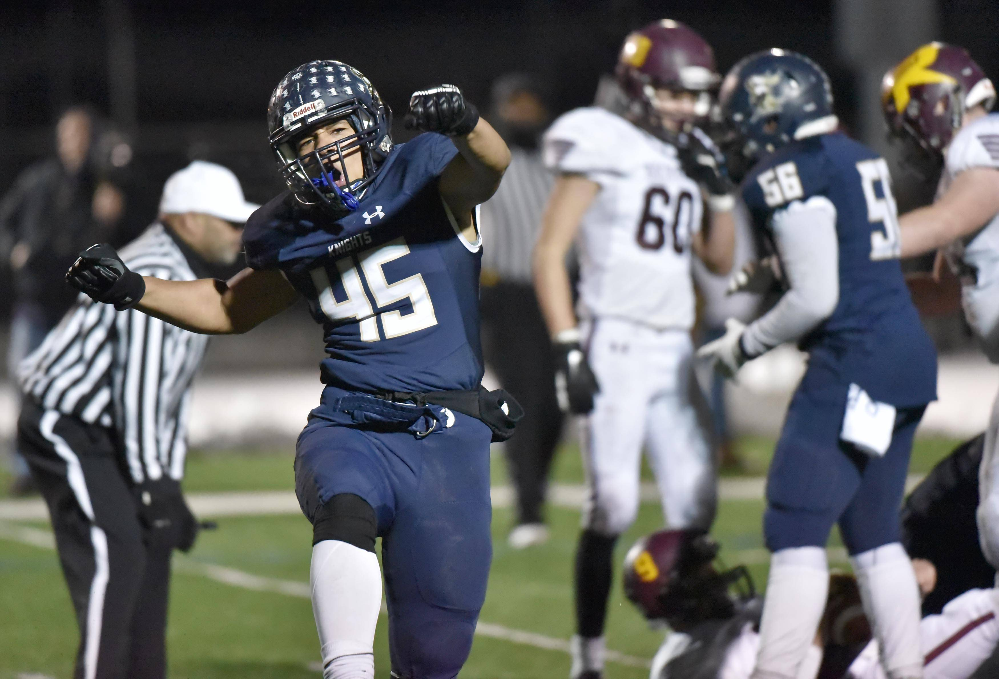 IC Catholic's Corties Draper celebrates his sack of Richmond-Burton's Jacob Huber, along with teammate Kevin Akins in the last minutes of a semifinal football playoff game Saturday in Elmhurst.