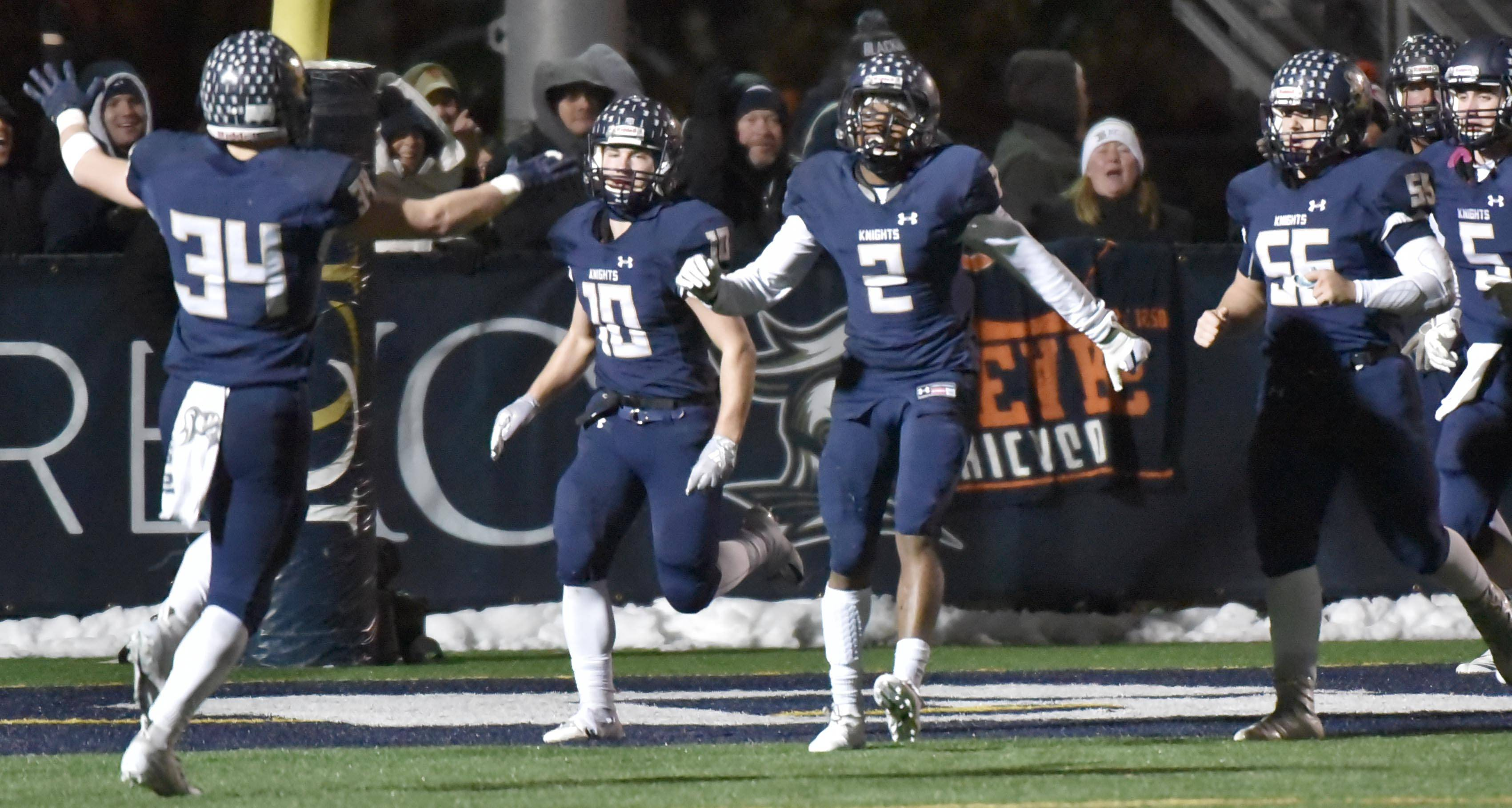 IC Catholic's Chauncey Lee celebrates with teammates after his interception return for a touchdown in the final minutes of the Knights win against Richmond-Burton in a semifinal football playoff game Saturday in Elmhurst.