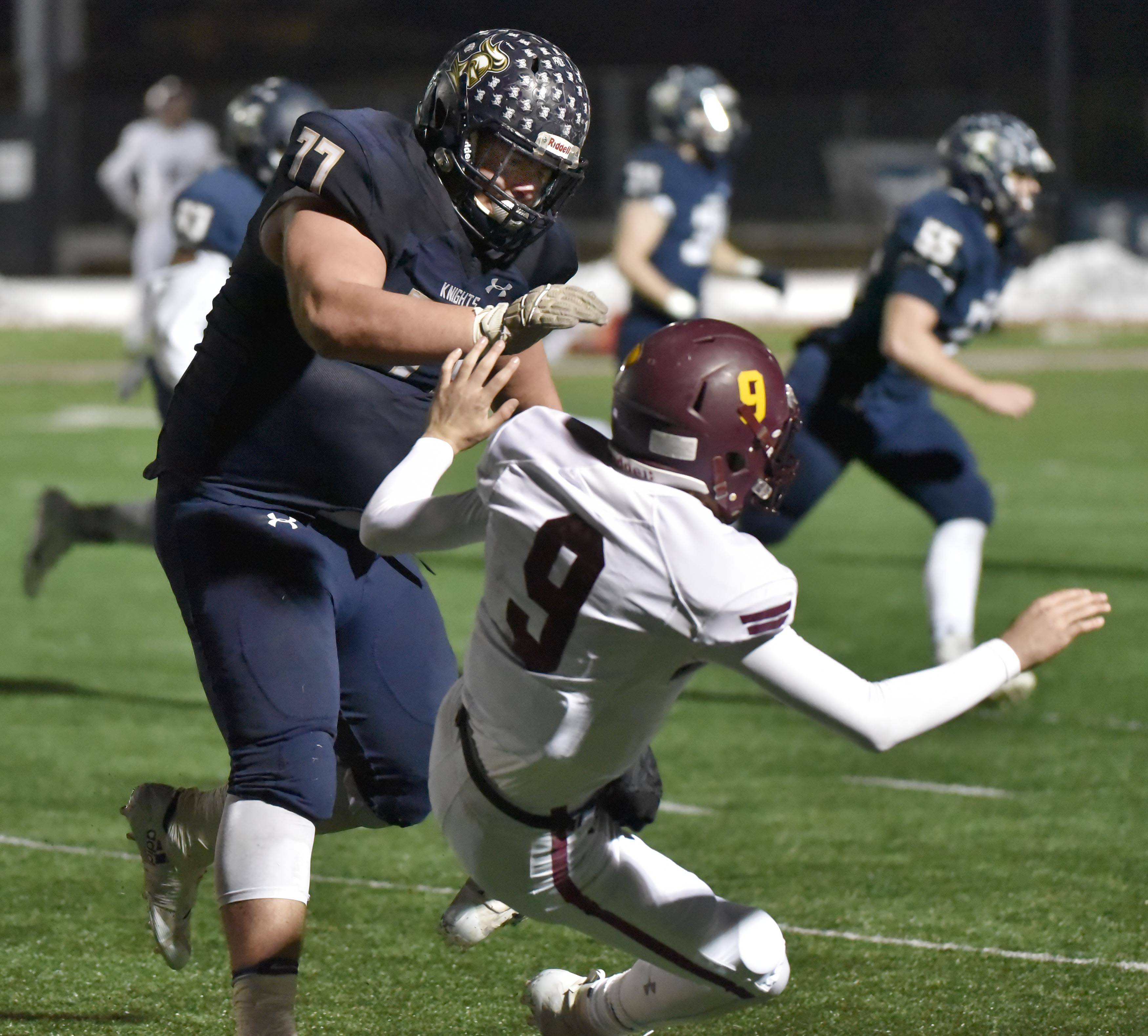 IC Catholic's Ricky Mysliwiec knocks Richmond-Burton quarterback Jacob Huber to the turf in the fourth quarter in a semifinal football playoff game Saturday in Elmhurst.