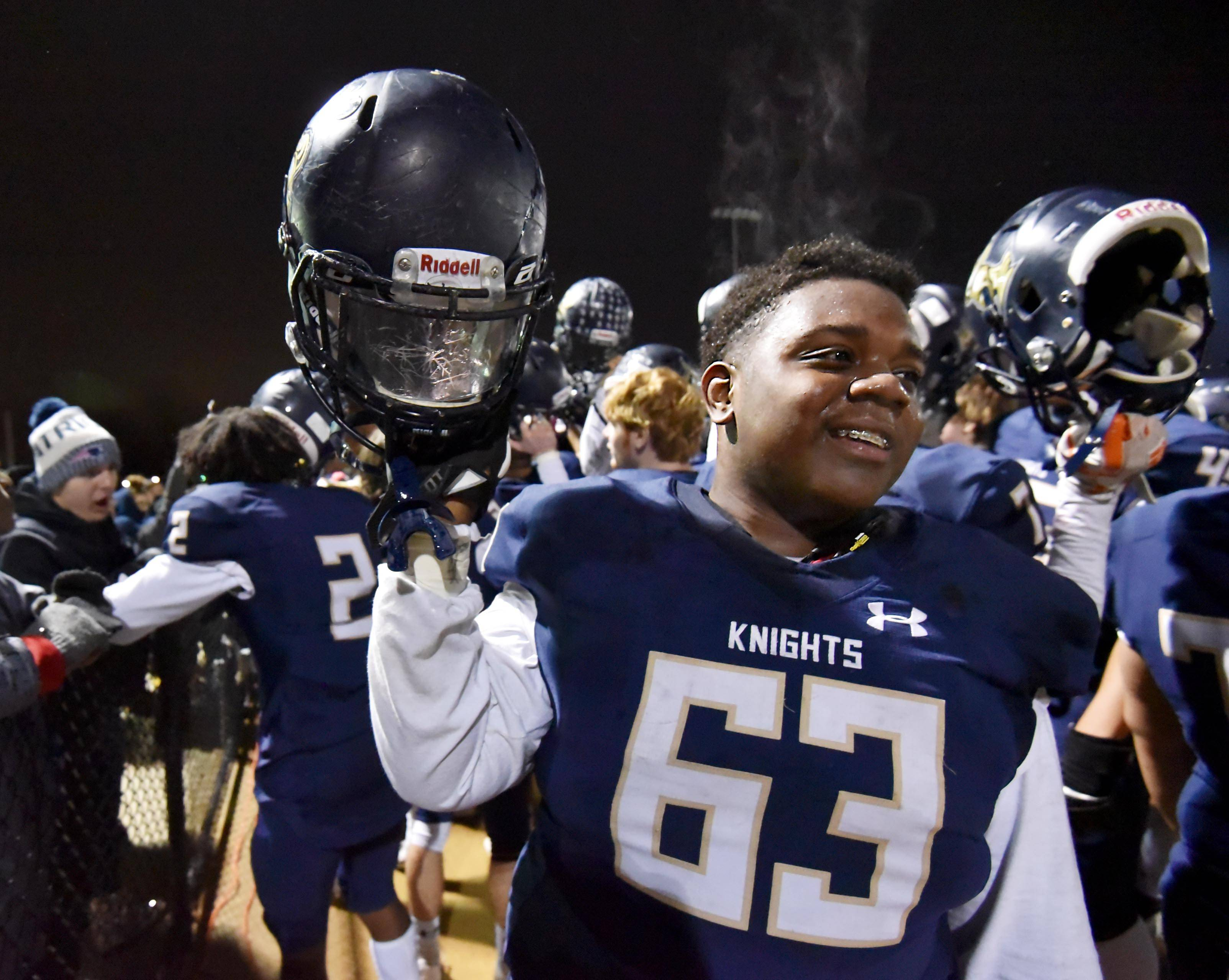 Steam rises off sweaty IC Catholic defensive lineman Koby Reed as the Knights celebrate their win over Richmond-Burton in a semifinal football playoff game Saturday in Elmhurst.
