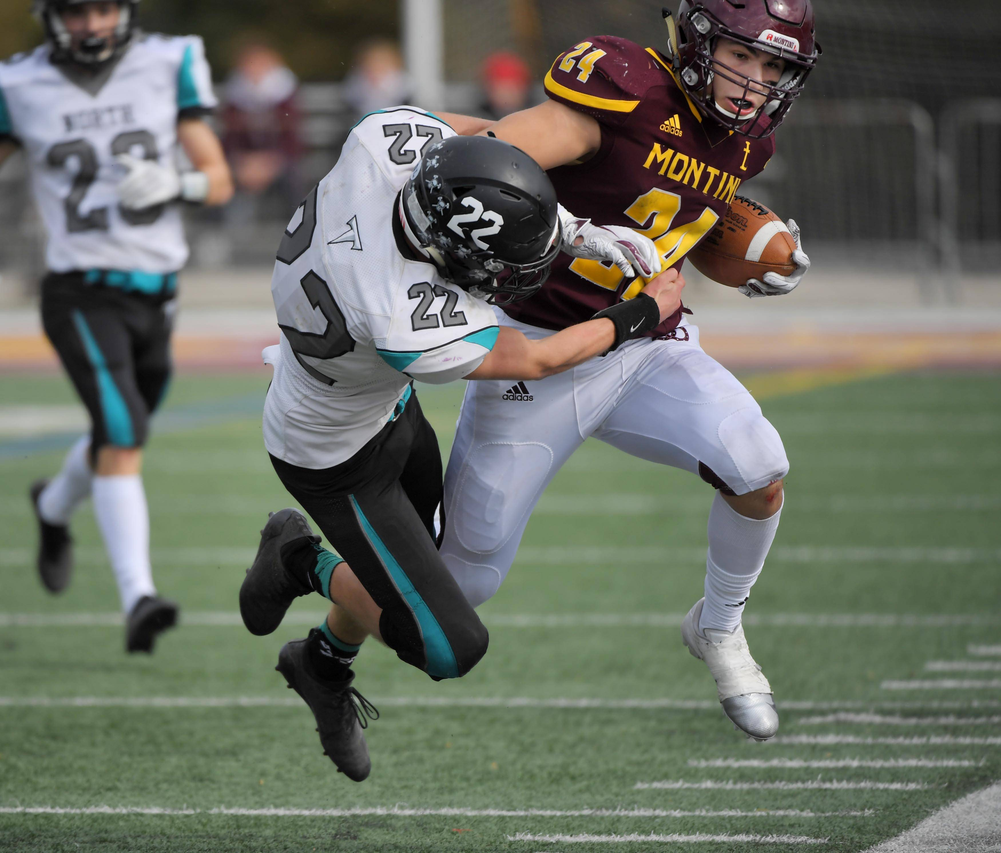 Montini's Nick Fedanzo is forced out of bounds after a long run by Woodstock North's Zachary Stopczynski in a playoff football game in Lombard Saturday.