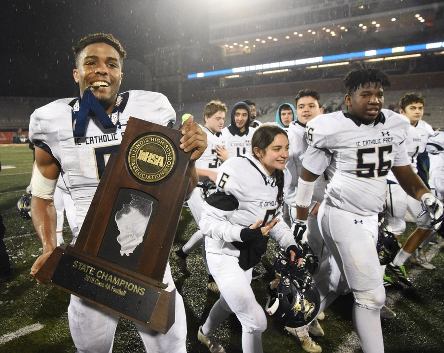 IC Catholic quarterback Khalil Saunders carries his team's trophy after the Class 4A football championship game against Bishop McNamara at Memorial Stadium in Champaign Friday. IC Catholic won the game 31-21.
