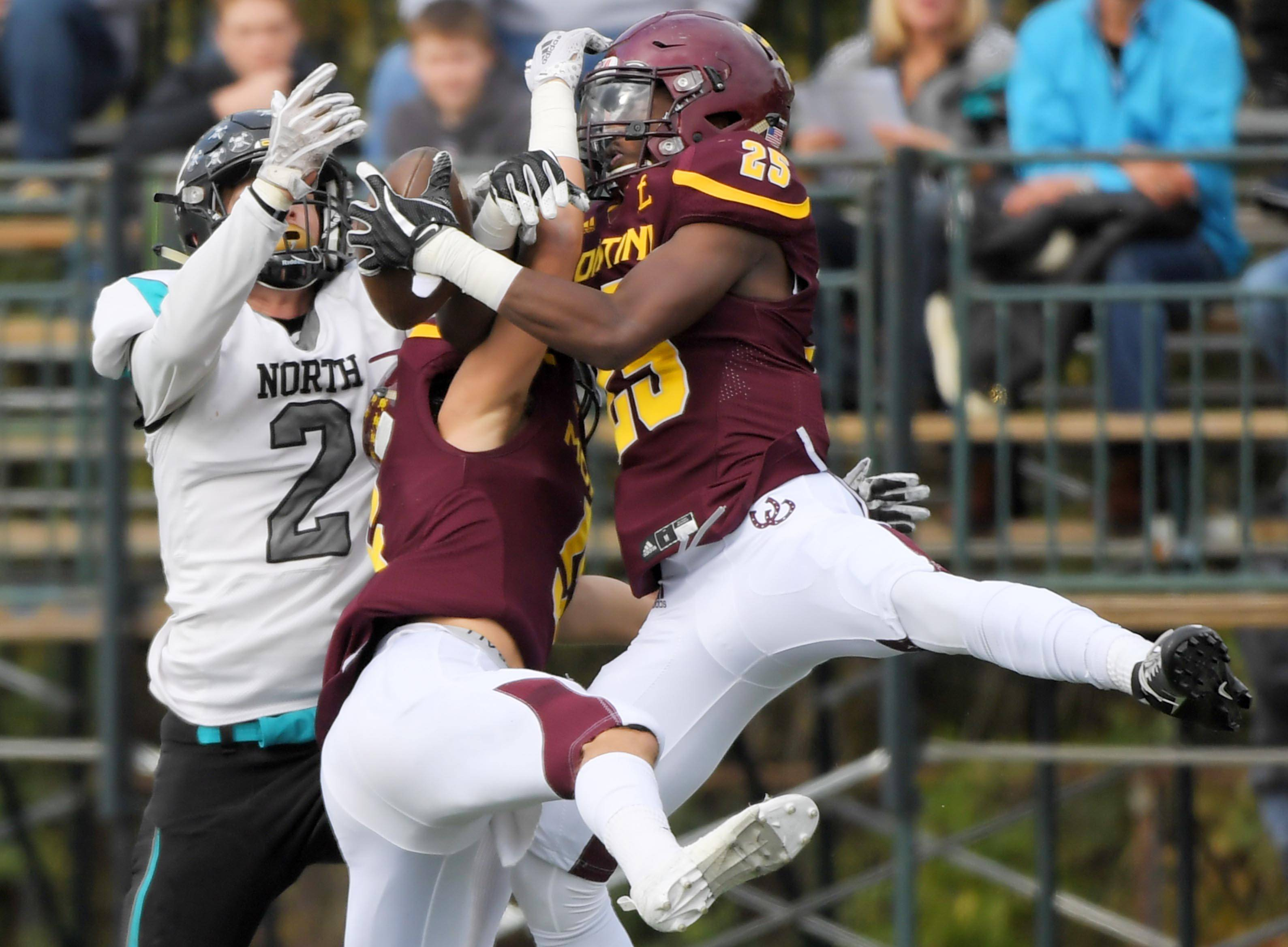 Montini's Jermari Harris intercepts a pass for Woodstock North's Carter Coalson as Montini's Ray Wojkovich also defends in a playoff football game in Lombard Saturday.