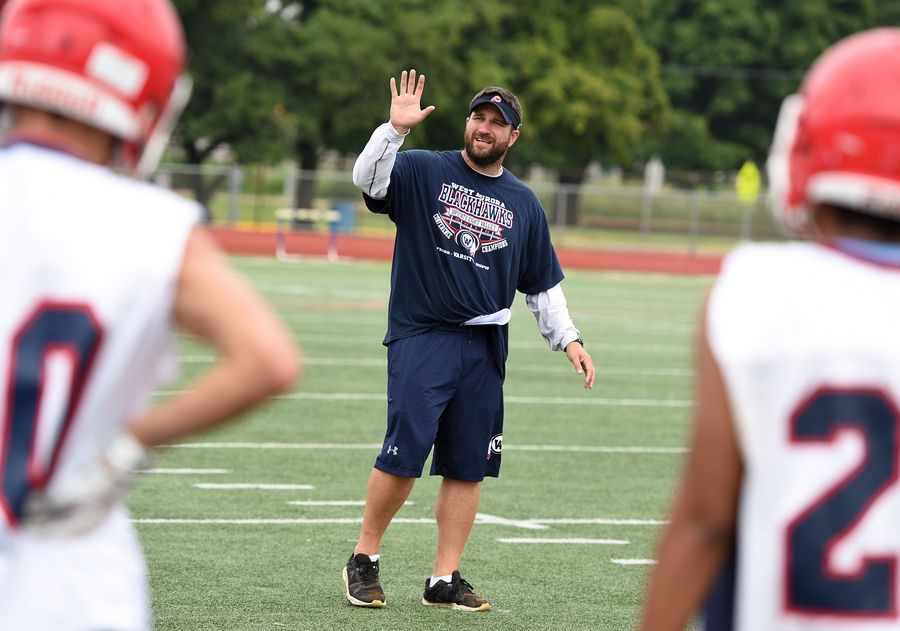 Head coach Nate Eimer works with his players during the first day of football practice at West Aurora High School Monday.
