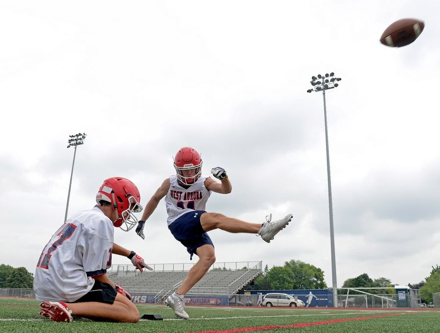 Logan Mont converts on a kick off a Sam Laurx hold during the first day of football practice at West Aurora High School Monday.