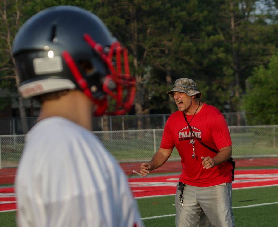Head coach Corey Olson gets the Palatine High School football team fired up during practice on Monday.
