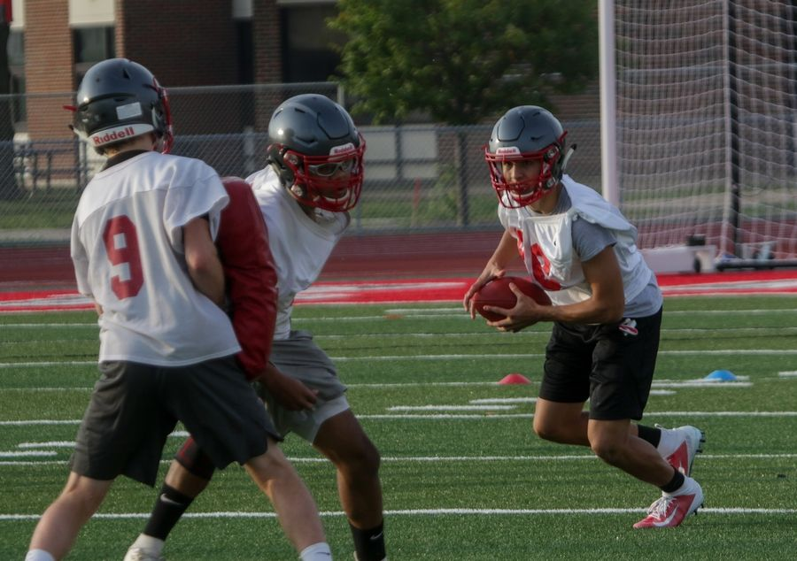 Luke Popovic, right, with the ball during Palatine High School football practice on Monday.