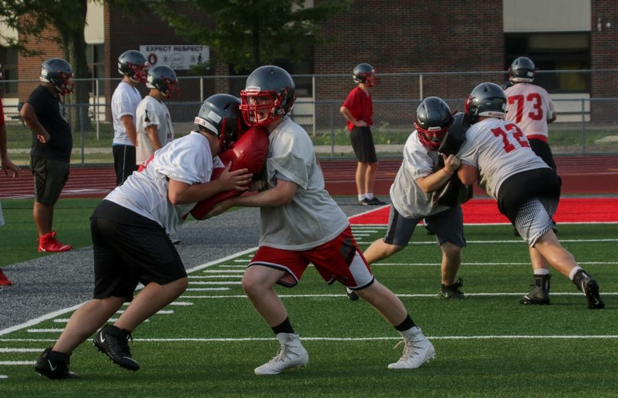 Players run through drills during Palatine High School football practice on Monday.