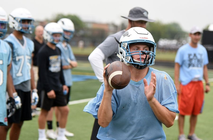 Quarterback Sam Tumilty rolls out to pass during the  first day of football practice at Willowbrook High School in Villa Park Monday.