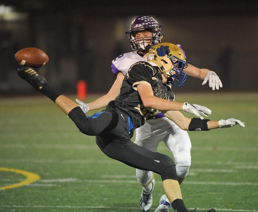 Wheeling's Danny Provost breaks up a long pass intended for Rolling Meadows' Charlie Svoboda last season.
